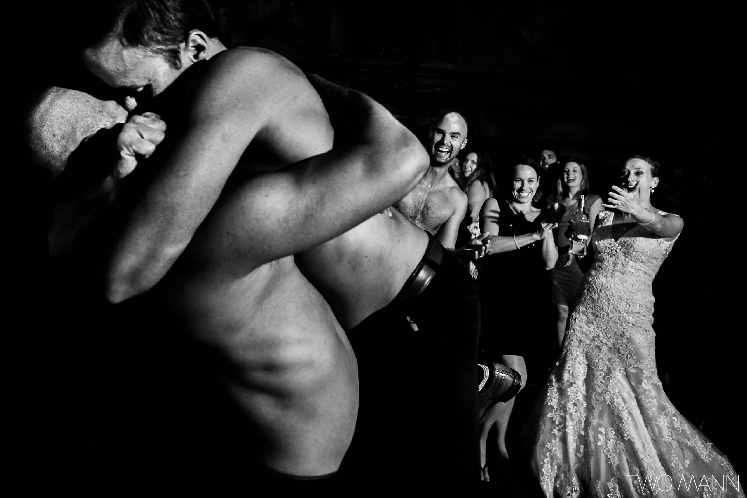 a bride and guest looking at two man dancing at reception party