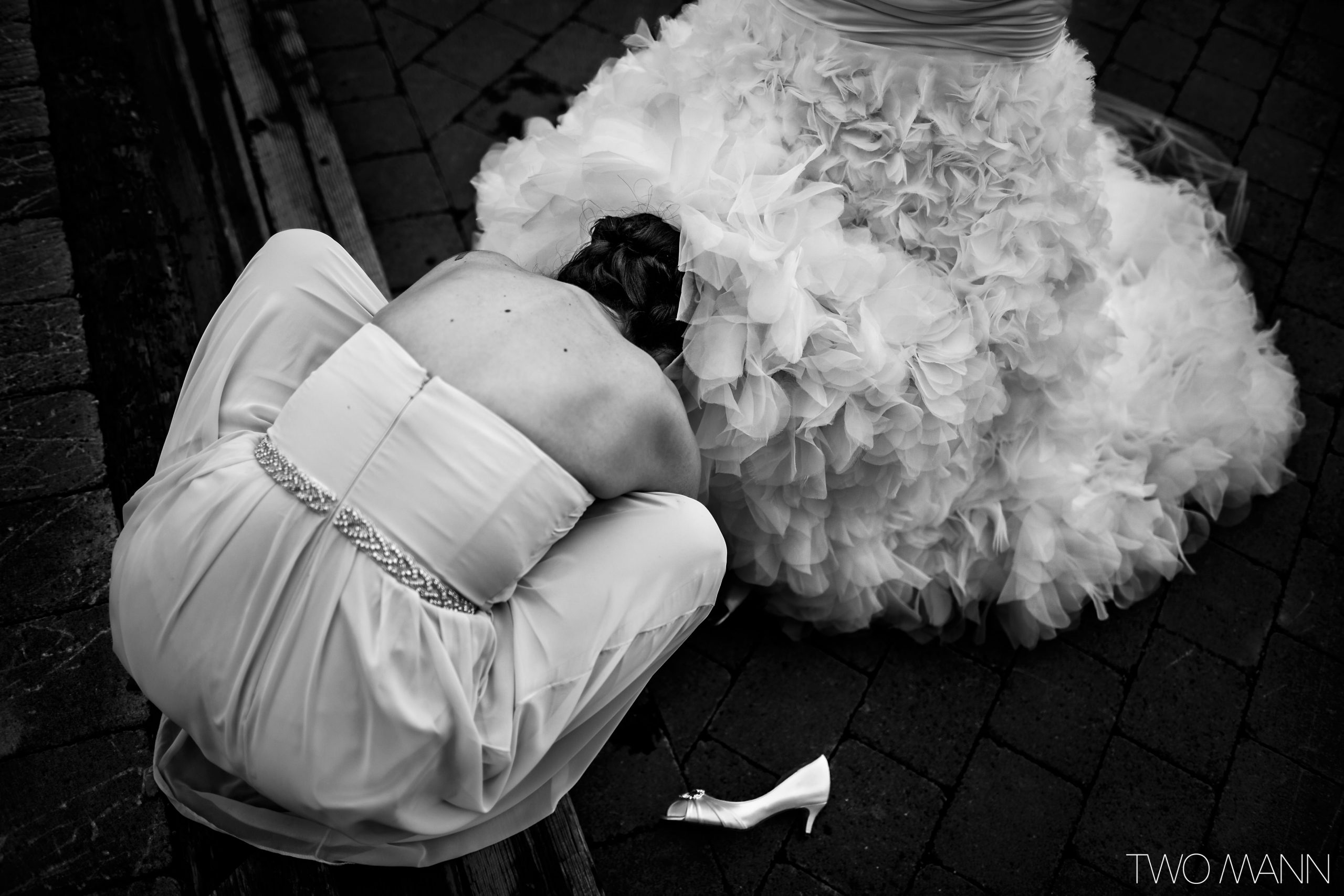 a bridesmaid help bride with her shoes under bride's dress hem
