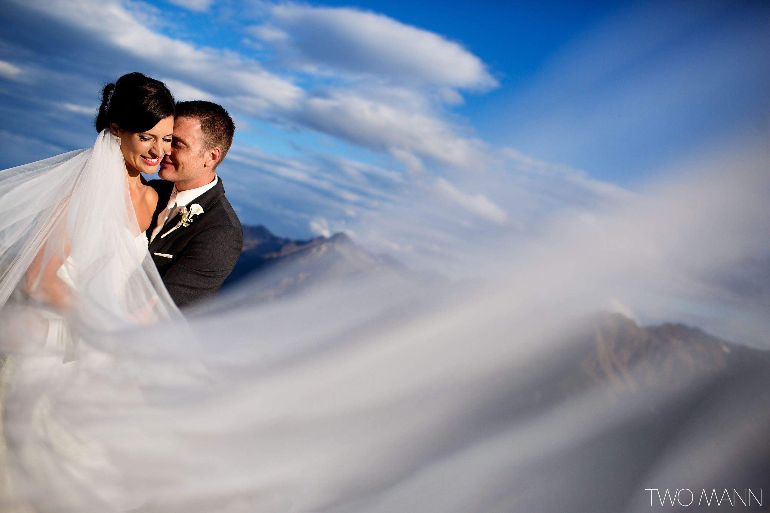 groom kissing bride on the cheek on mountain top with cloudy sky background