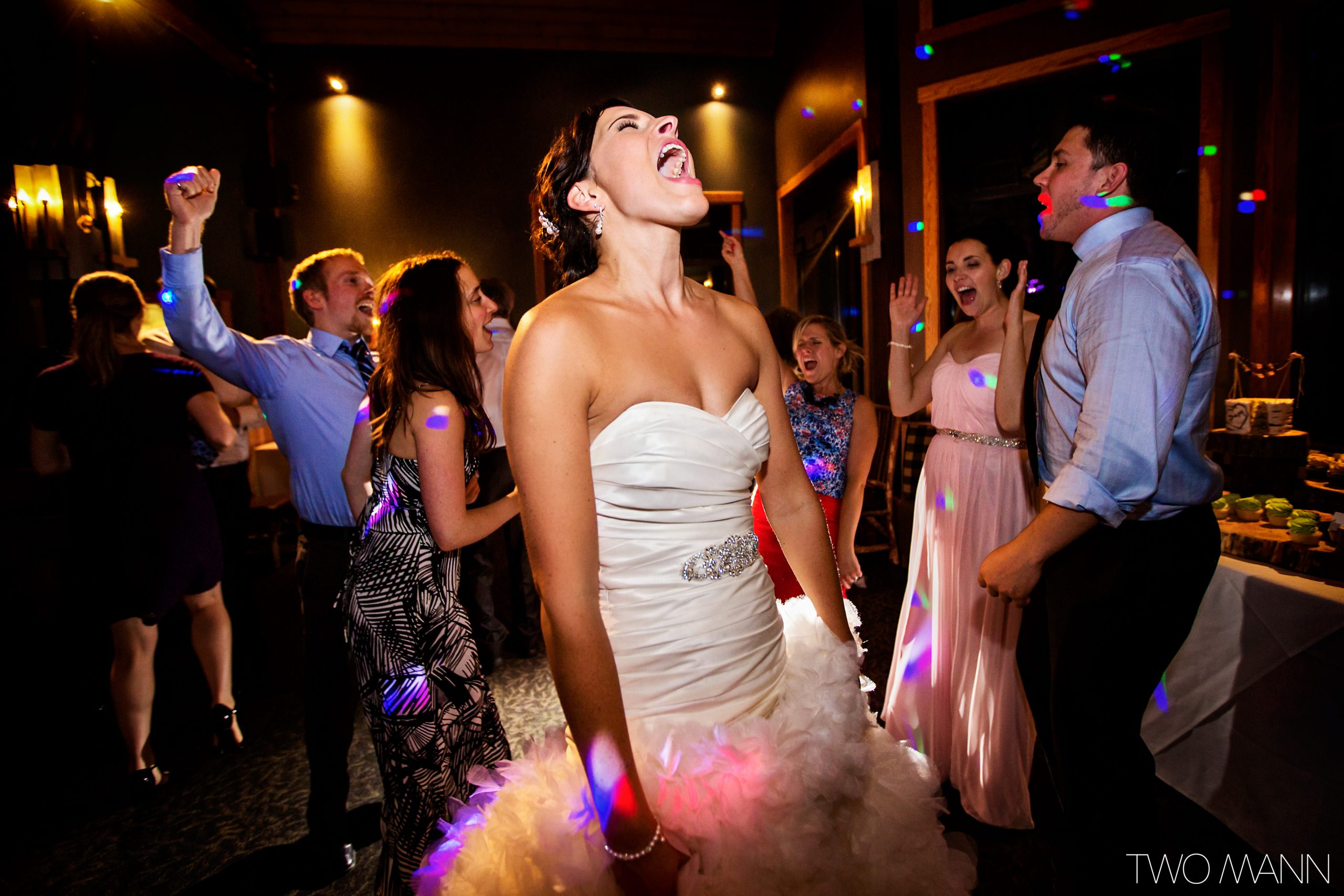 excited bride and wedding guests hitting the dance floor