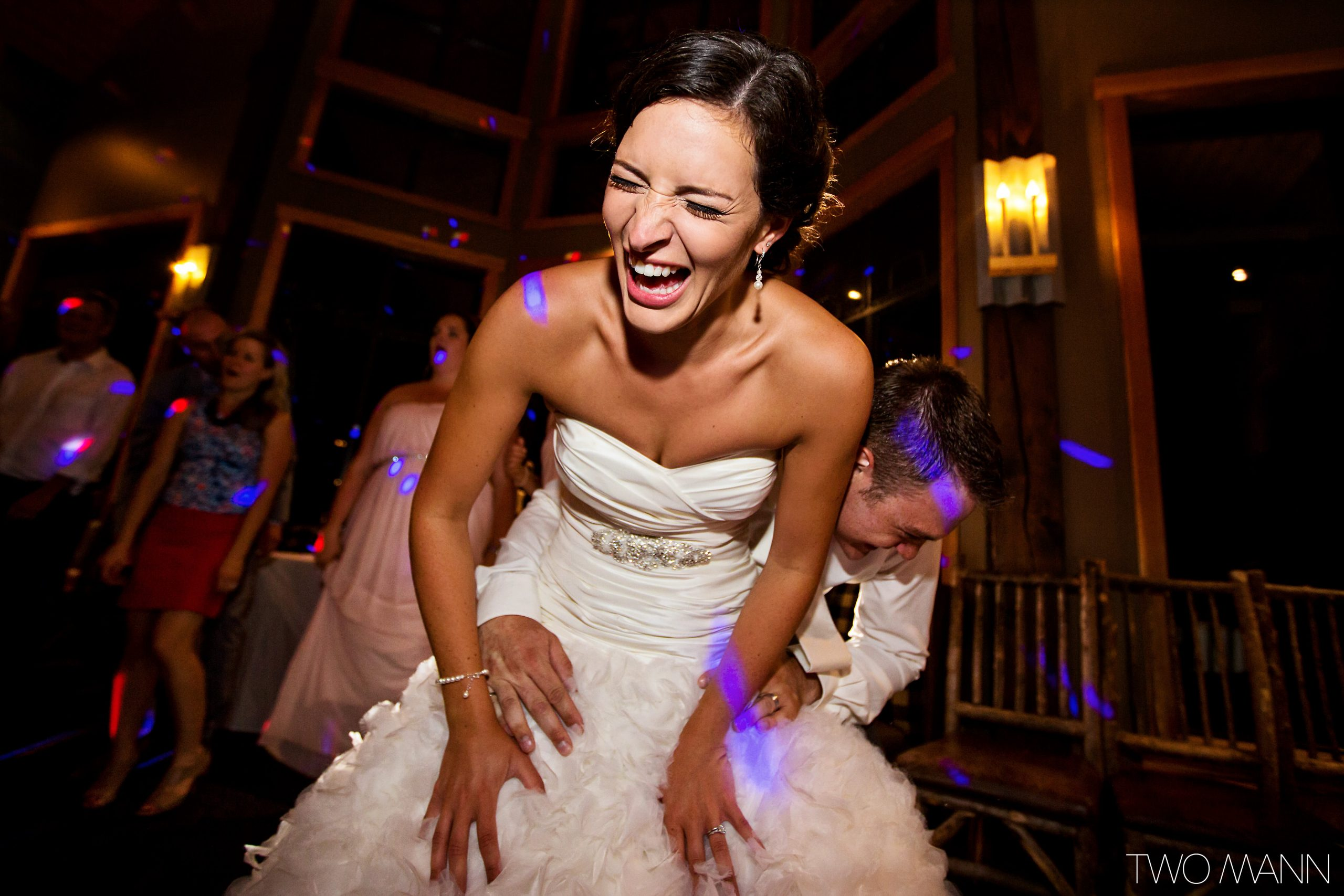 groom holding bride from back laughing at reception
