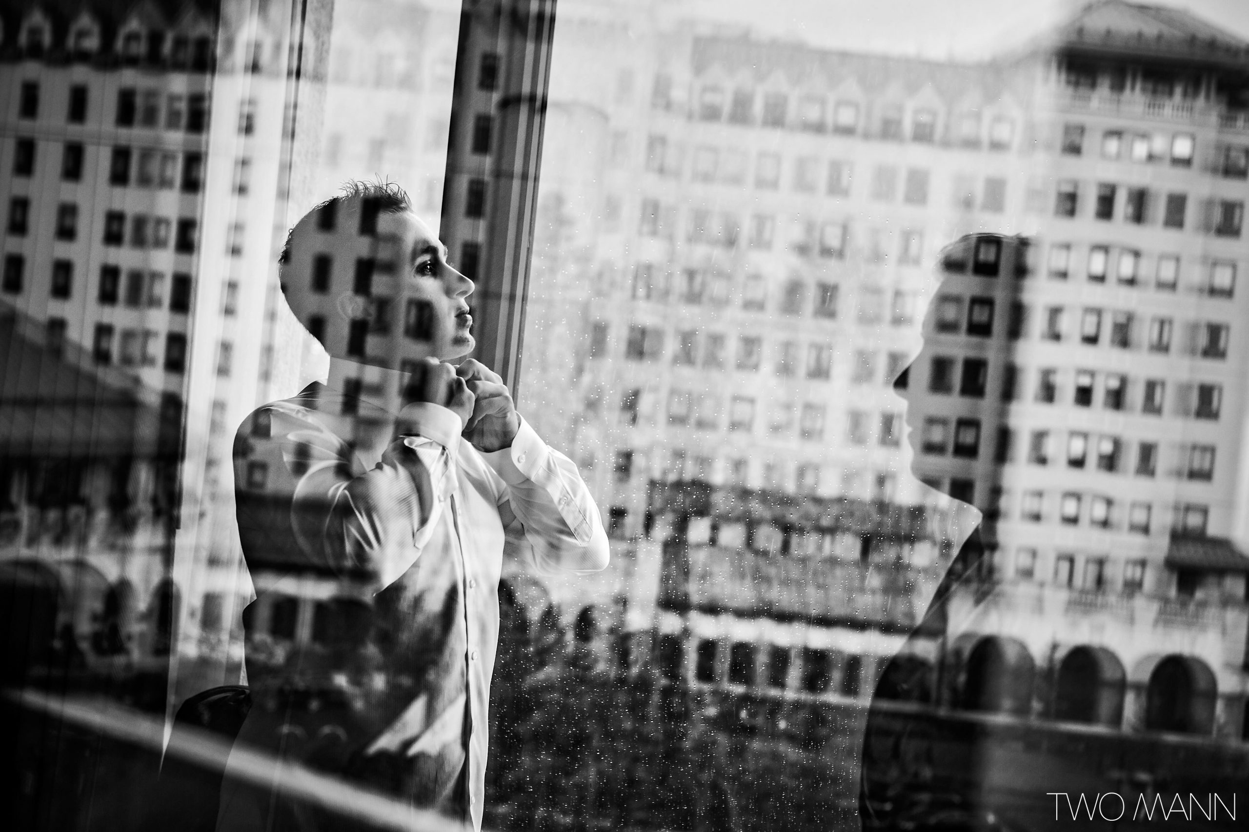 groom buttoning his dress shirt in front of a window reflecting Fairmont Chateau Lake Louise buildings