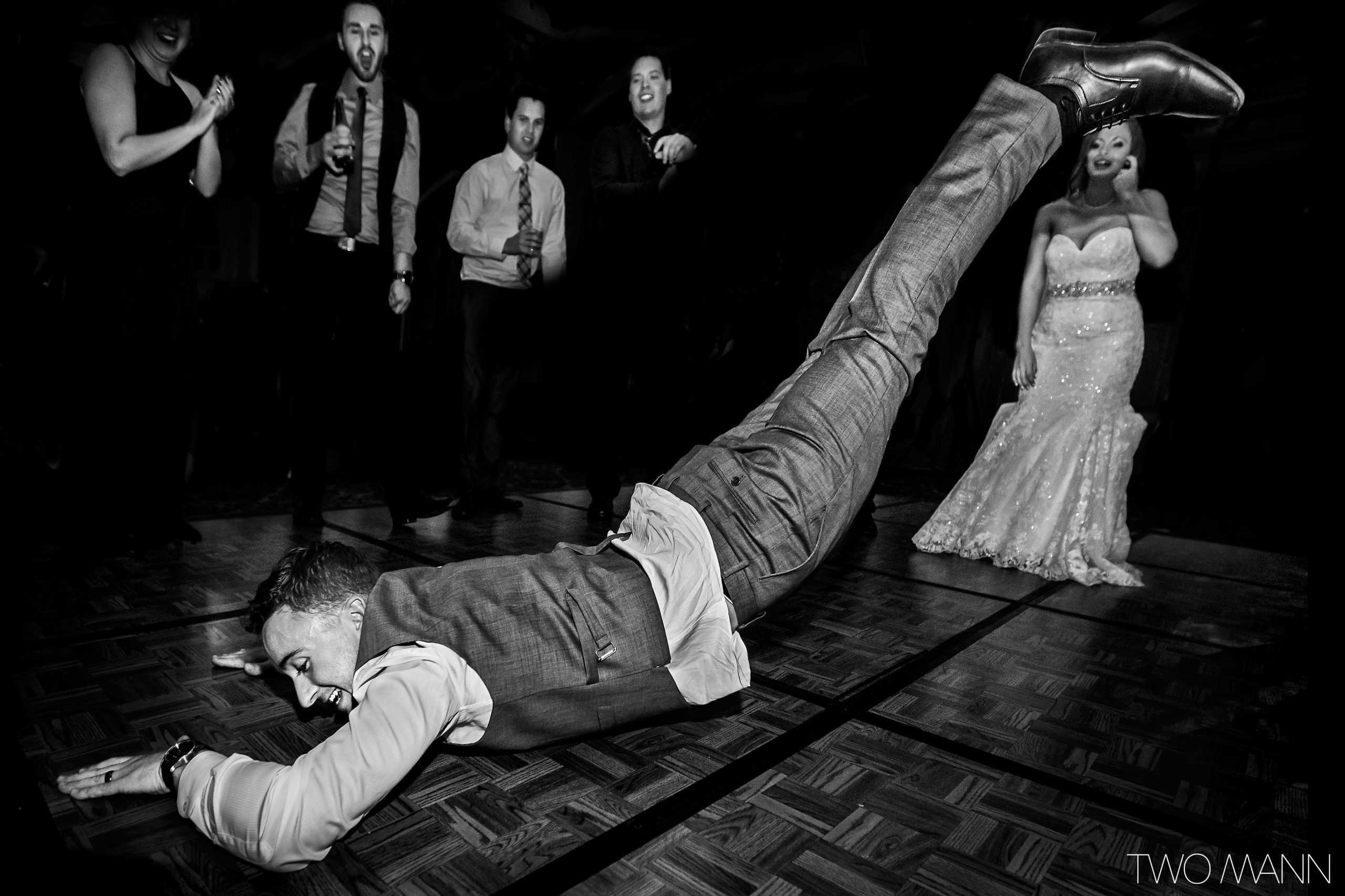 a groom hitting himself on the dance floor