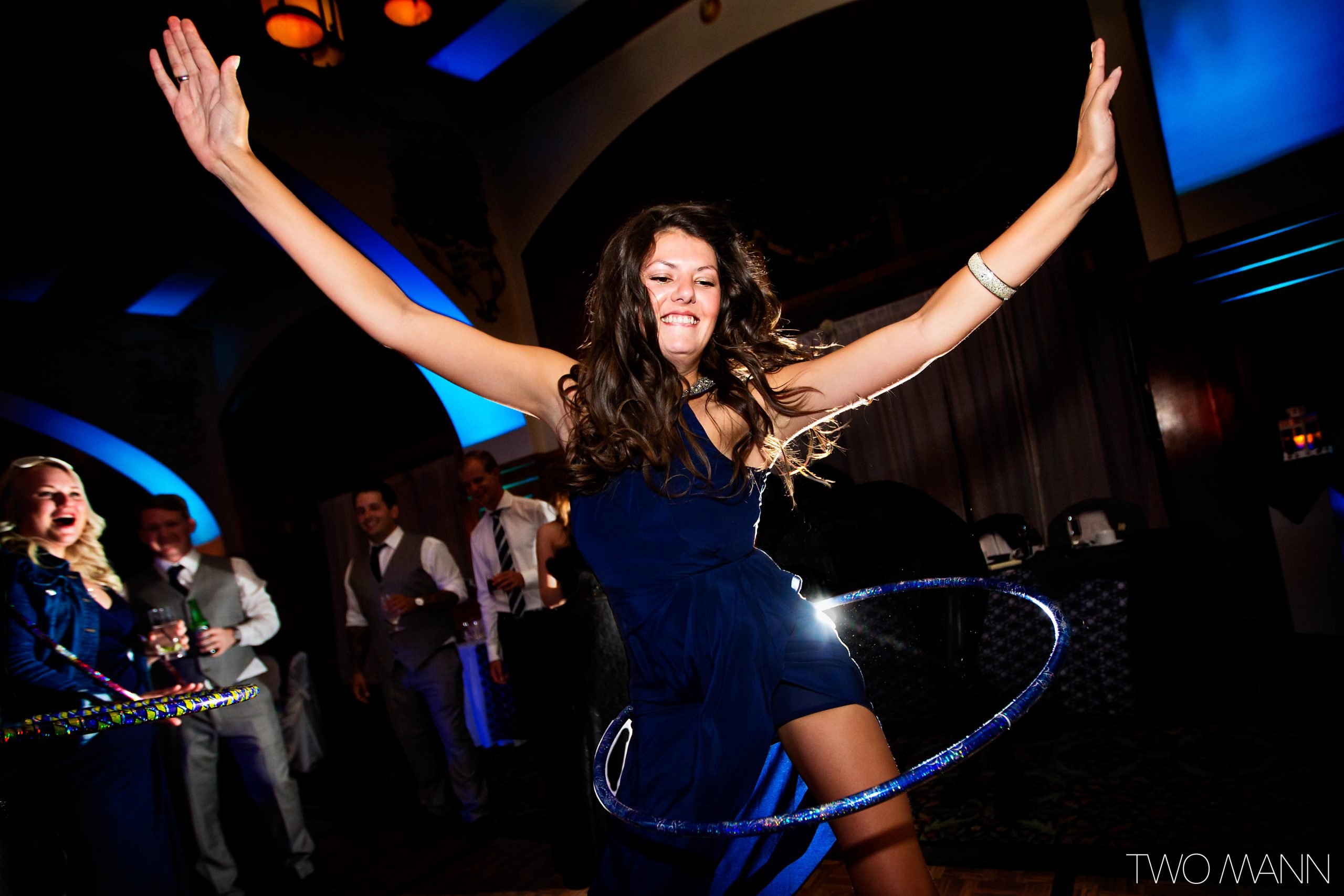 a lady dancing with a hula hoop at a wedding reception