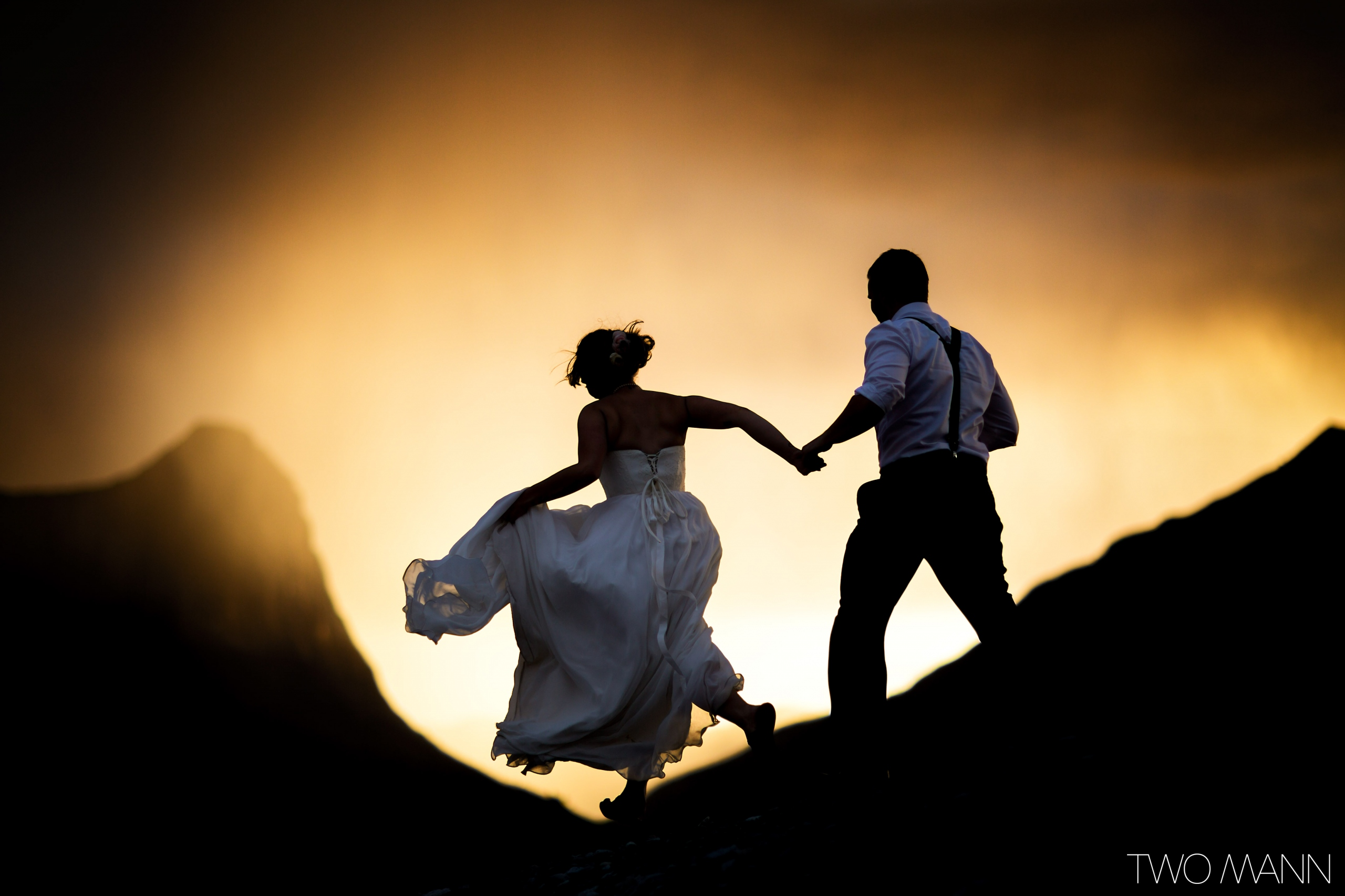 bride and groom holding hands and running on top of mountain at sunset in Canmore Canada