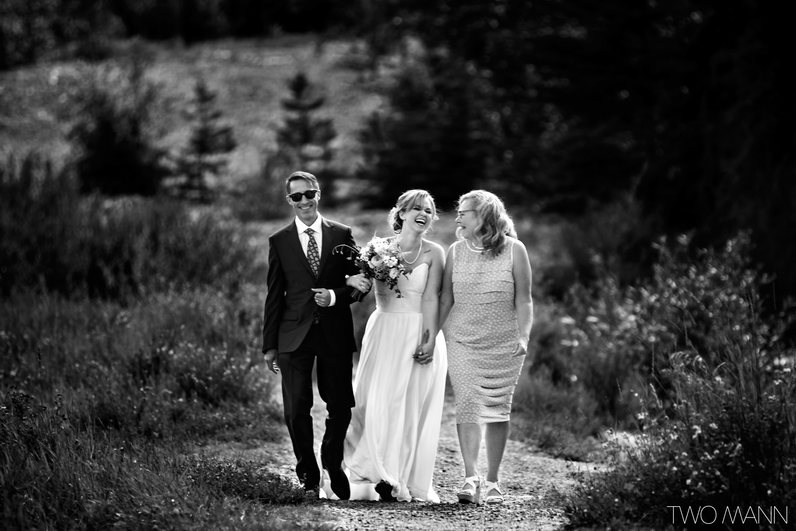 happy bride walking with parents in a forest
