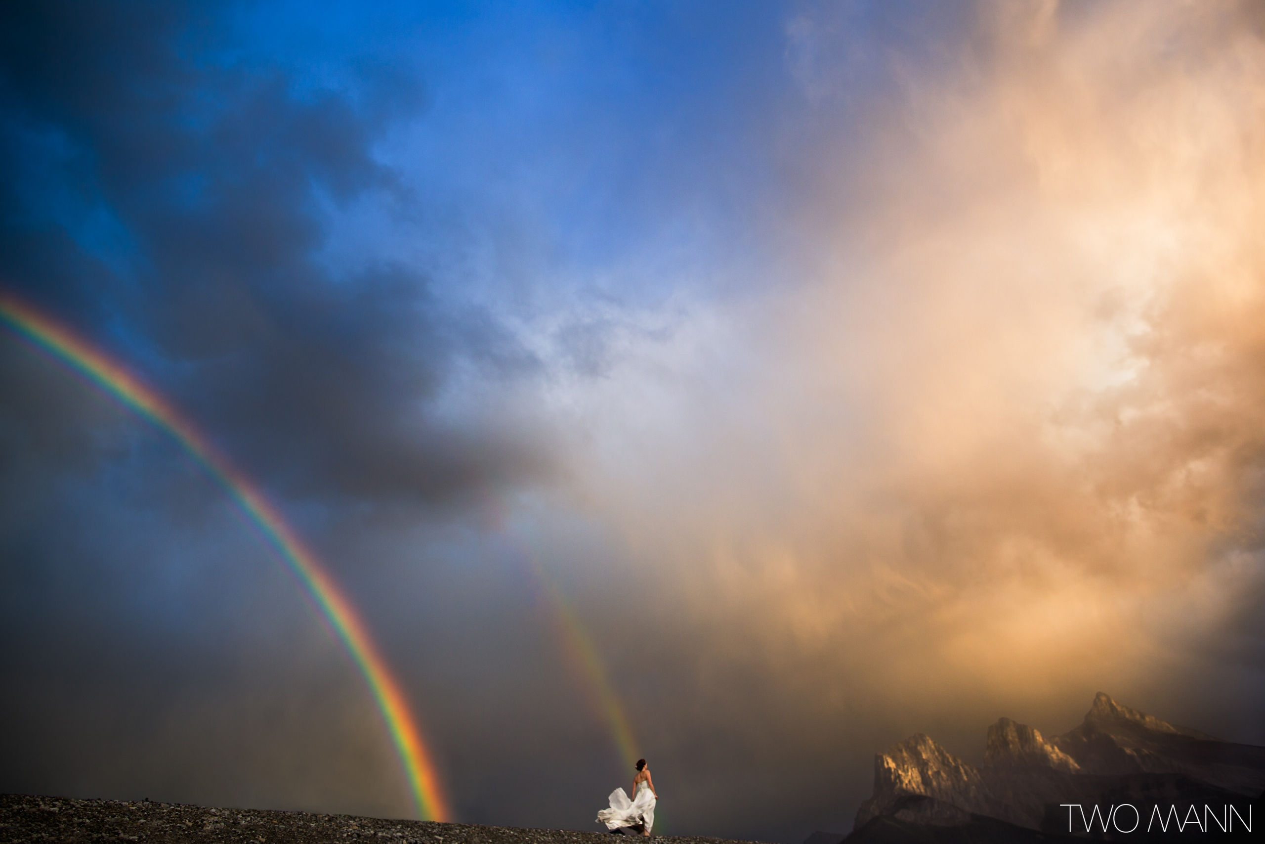 bride in wedding dress on mountain top with double rainbow in sky