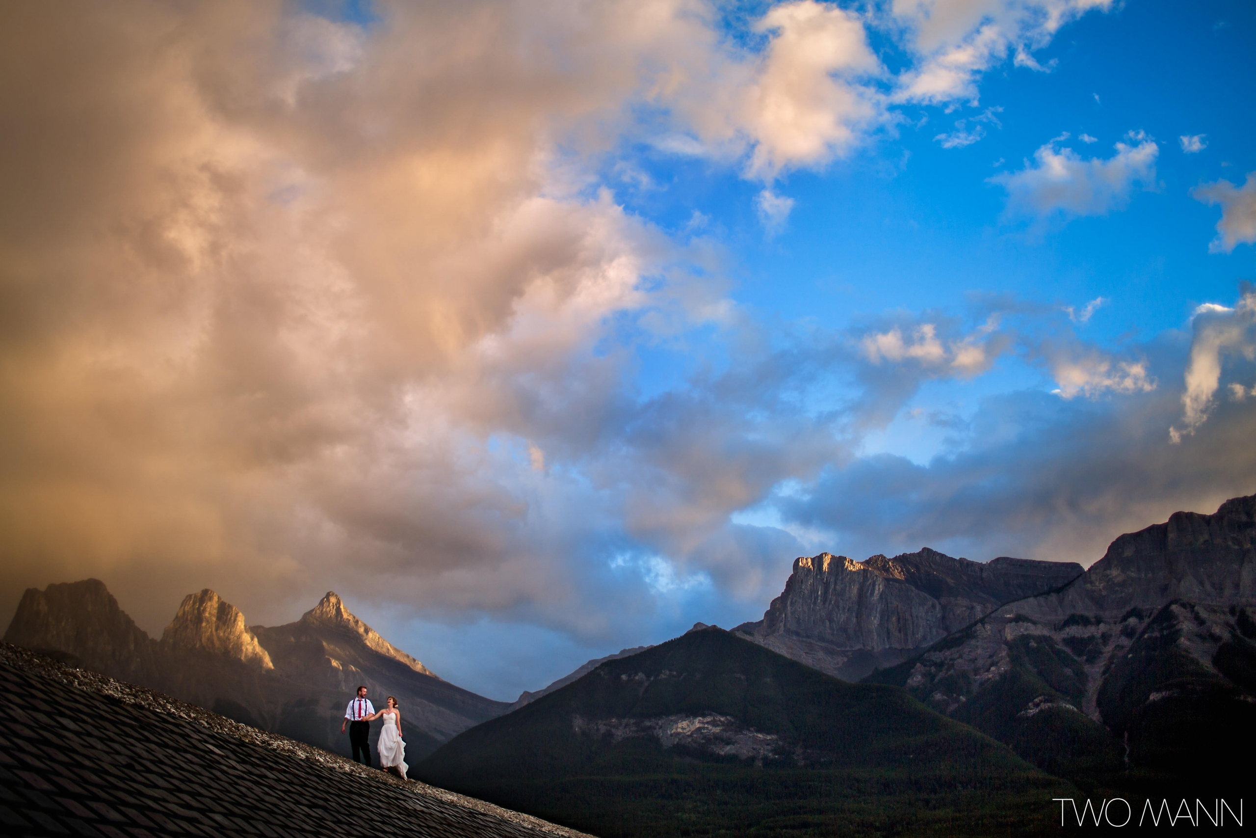 bride and groom walking on mountain slope with background of Canadian Rockies and cloudy sky