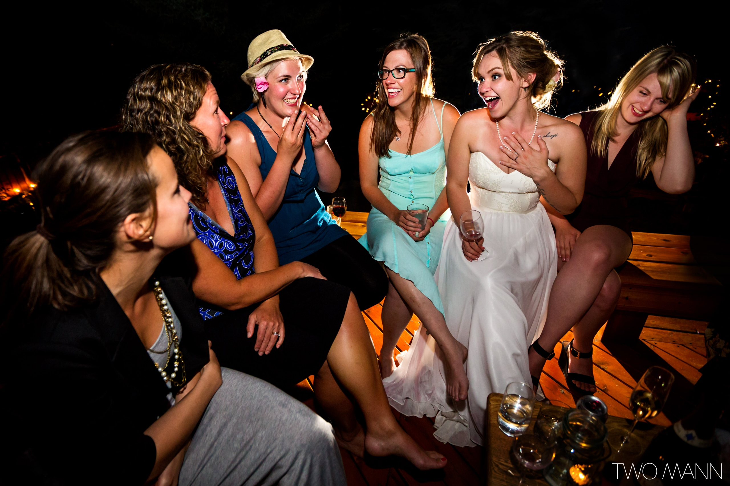 a bride sitting and chatting with girl friends on a deck at night