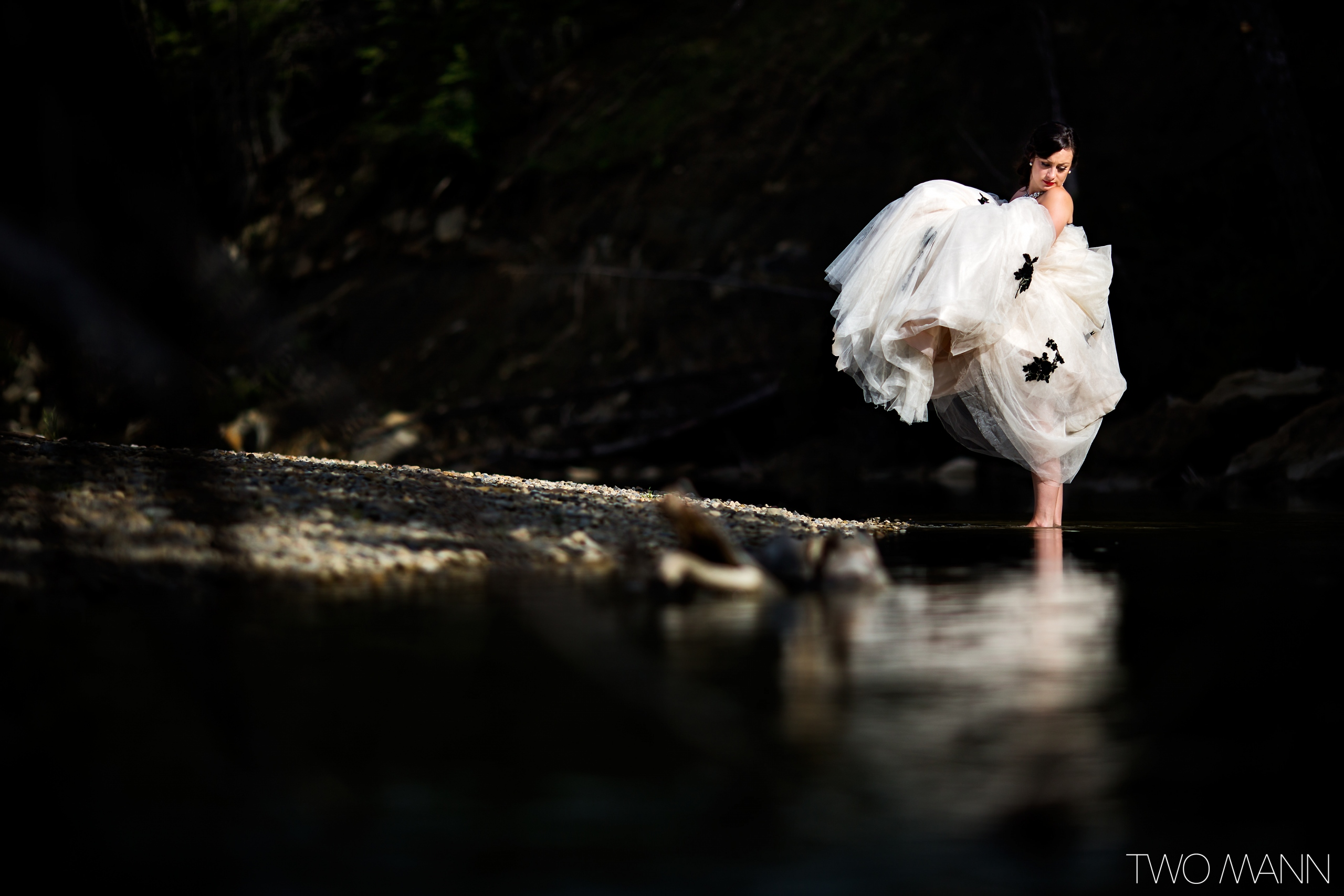 a bride standing in water holding up wedding dress train