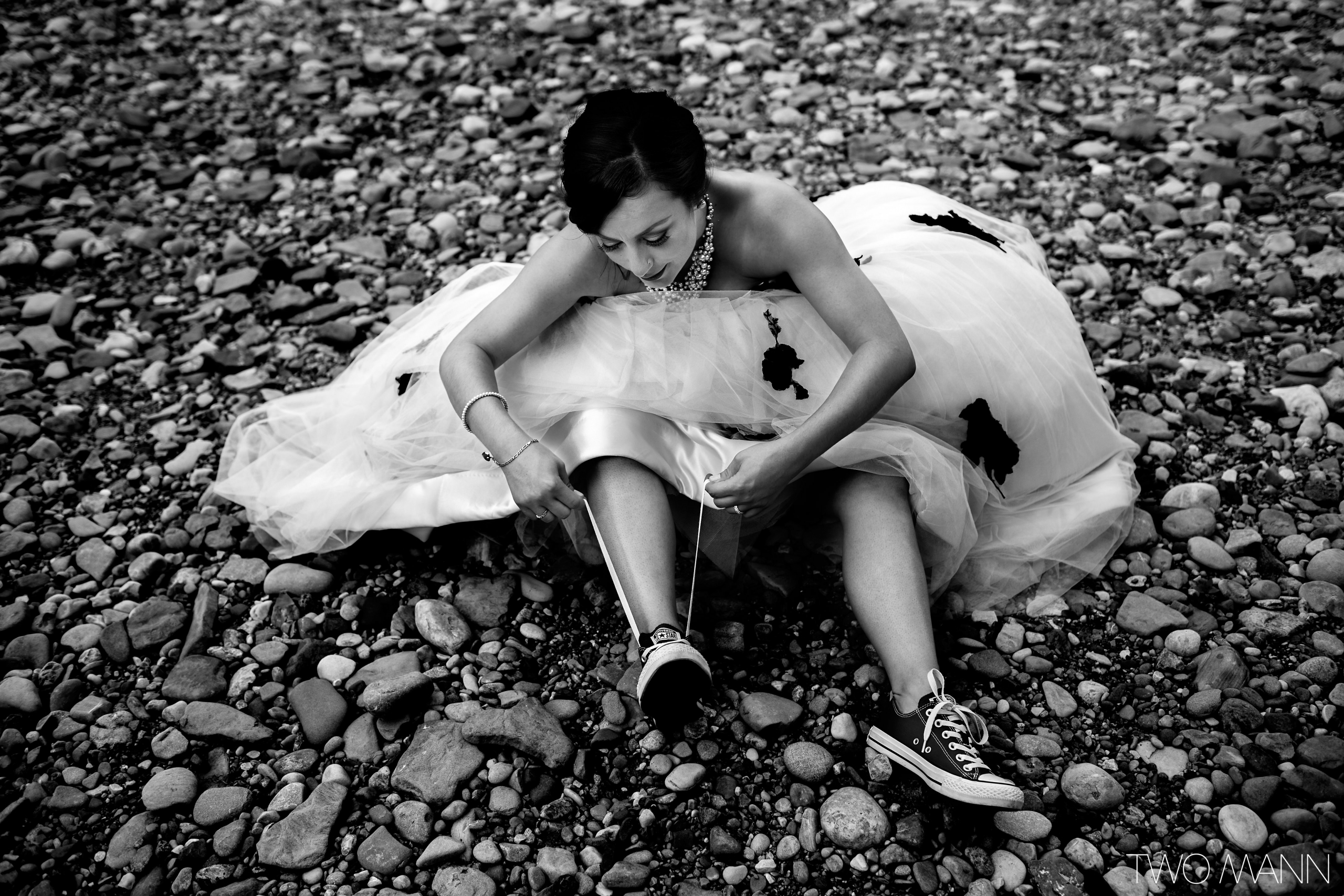 a bride sits on the river bank putting her shoes on