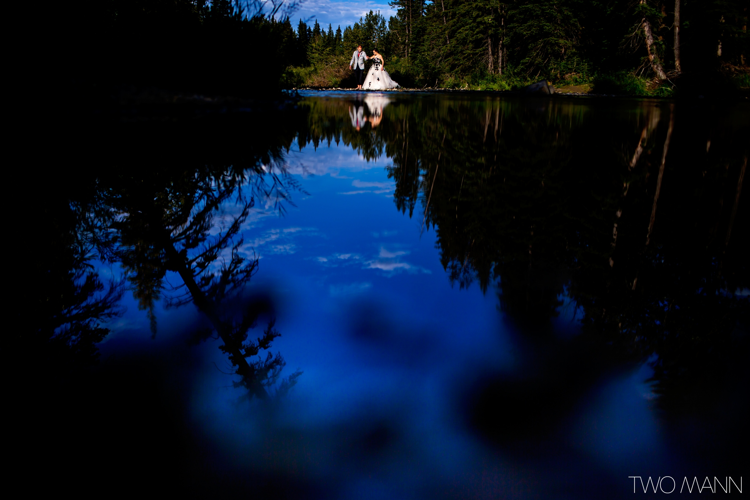 bride and groom walking on the shore of a river