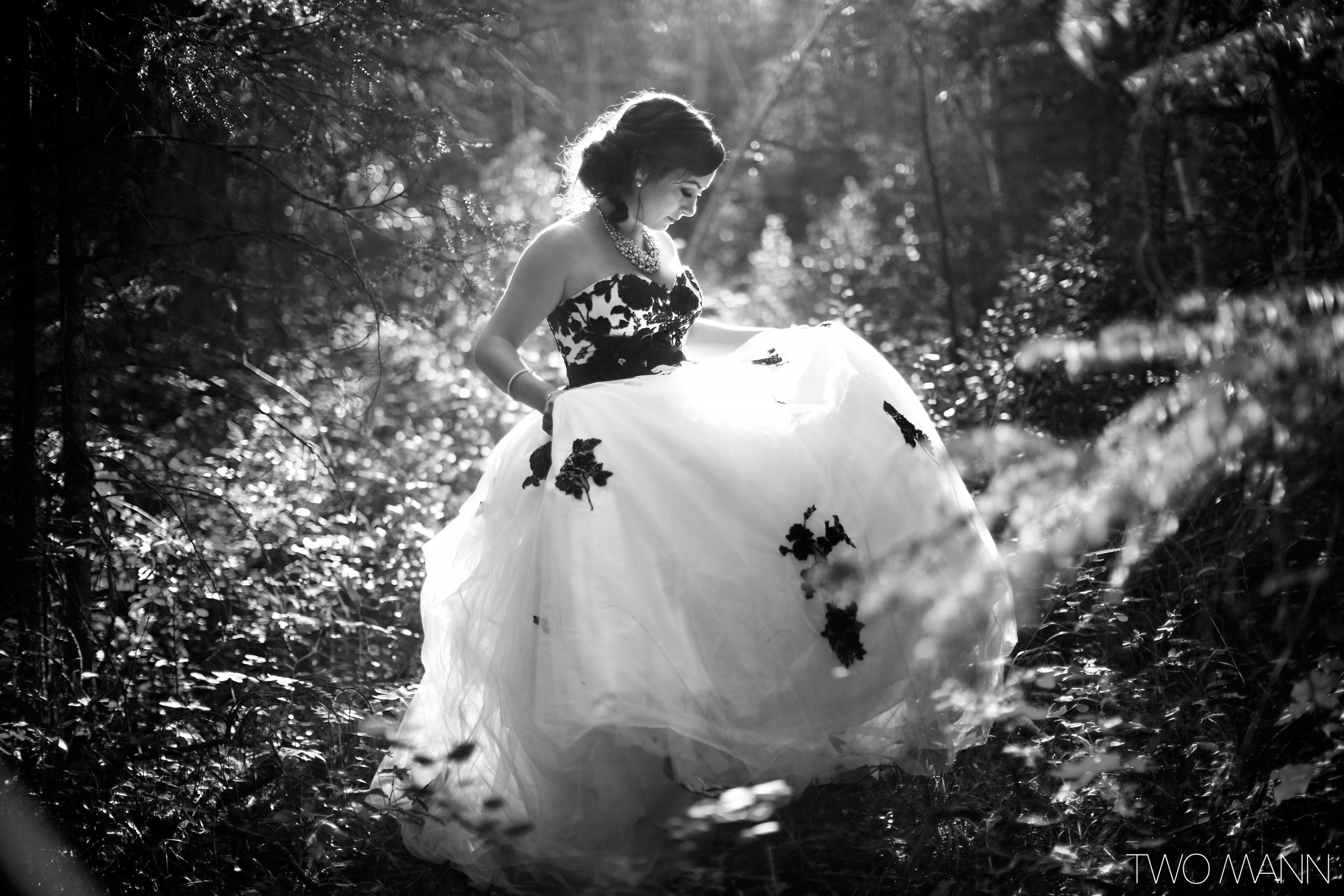 a bride bride poses in a forest under the sunshine
