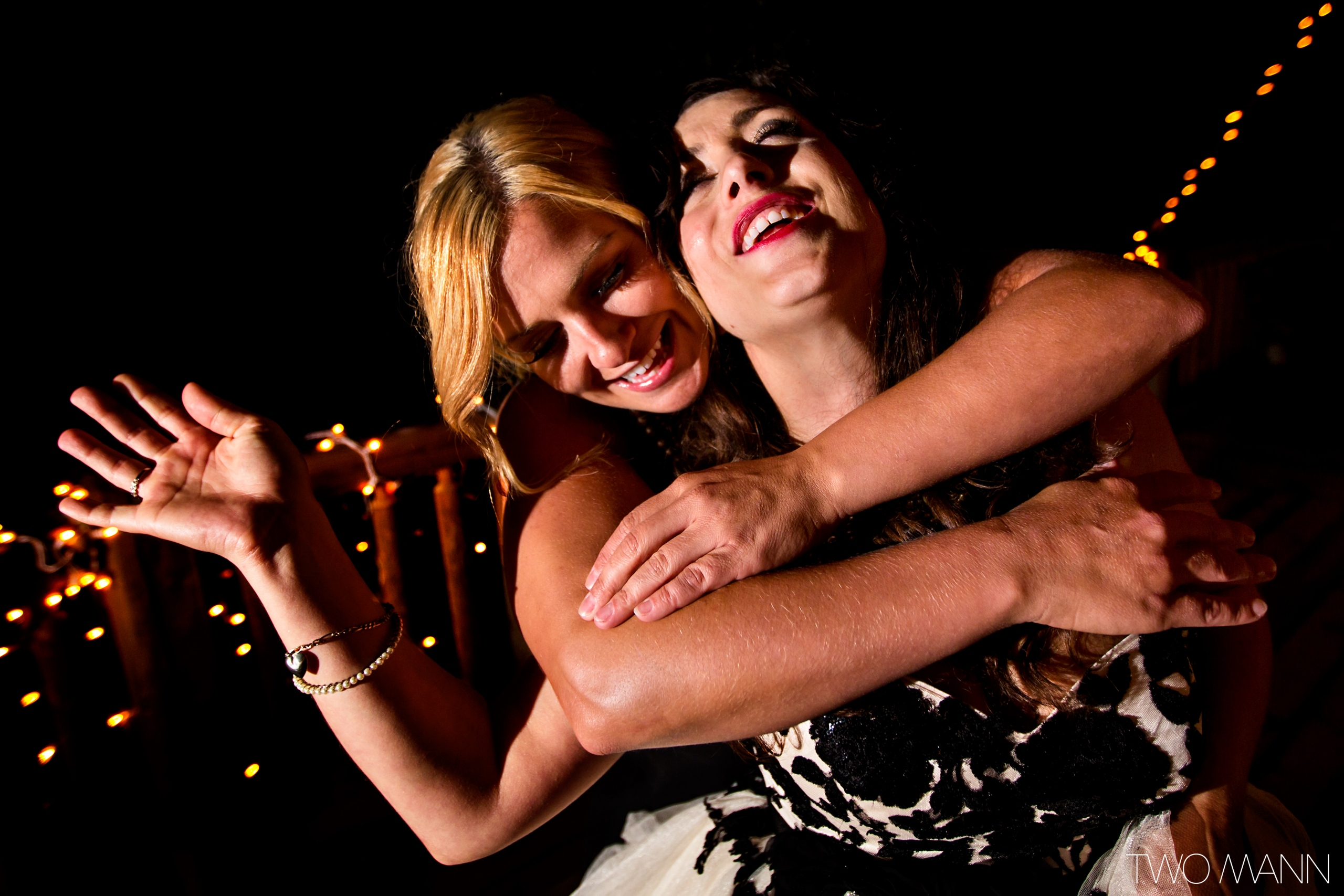 a friend hugs bride from back at reception