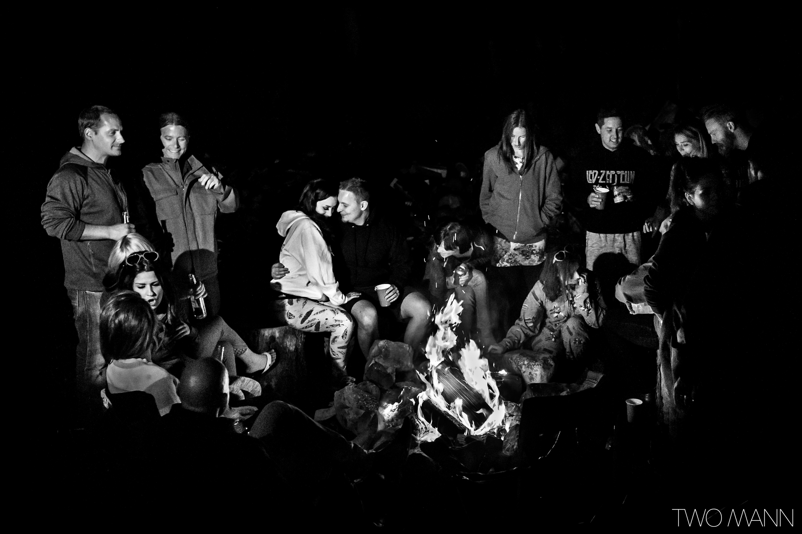 newlyweds and wedding guests around a bonfire