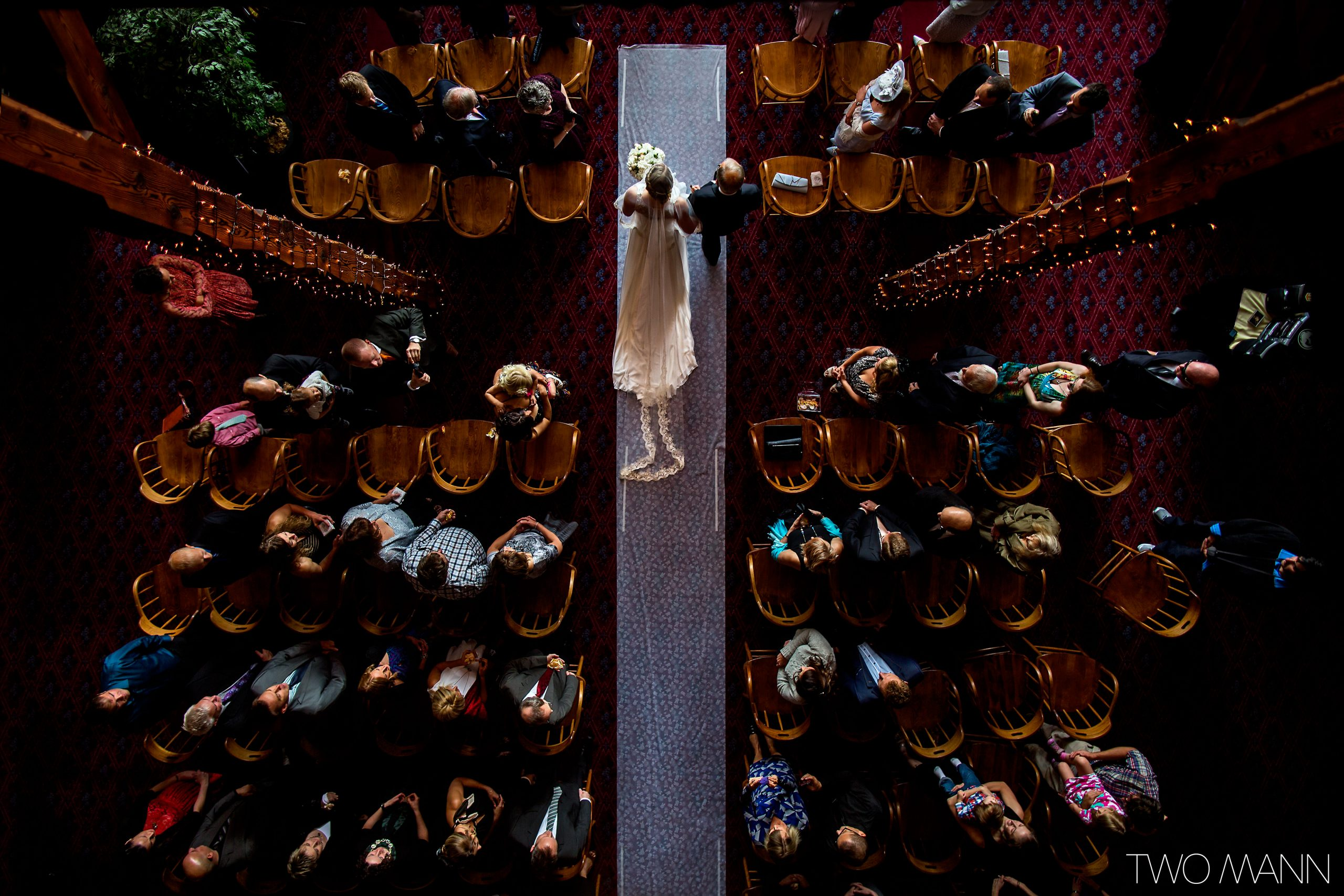 a bird's-eye view of father walking daughter down the aisle