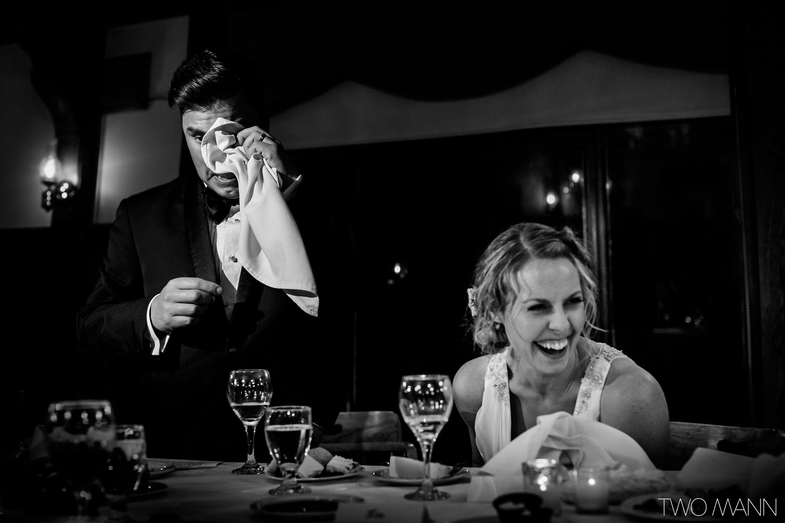tearful groom and smiling bride at wedding table