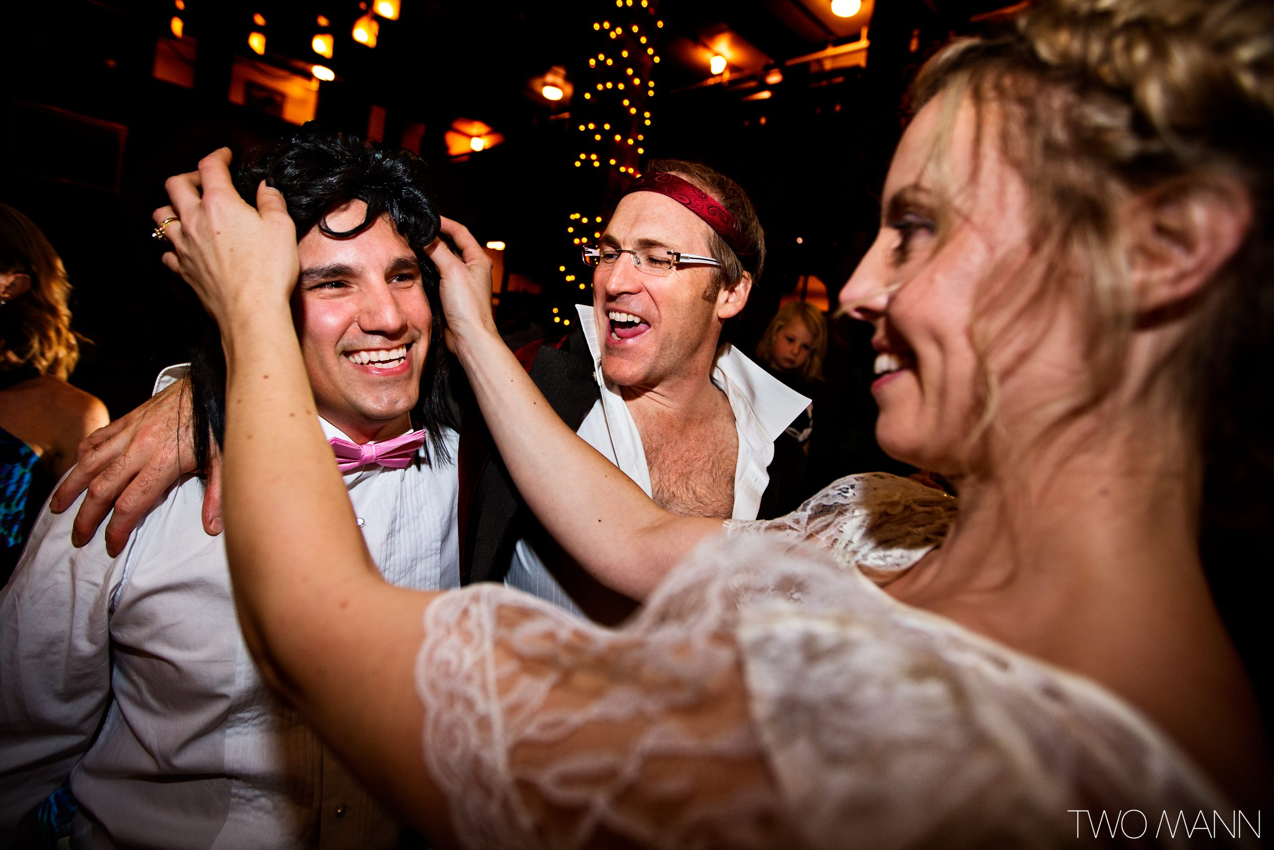 a bride putting on a wig for the groom at retro 80's reception dance party