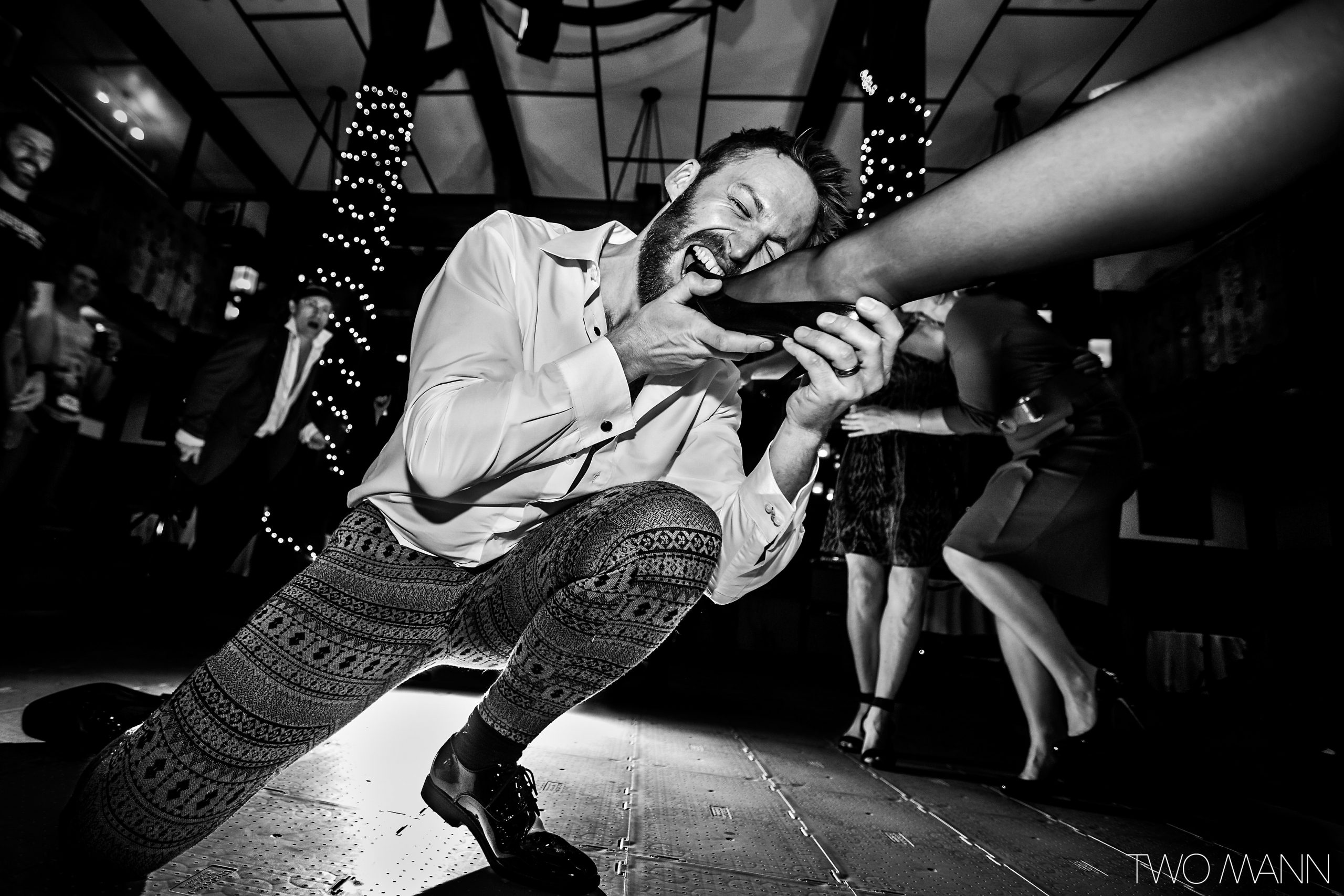 a groom kneeling down to take bride's foot in a dance move