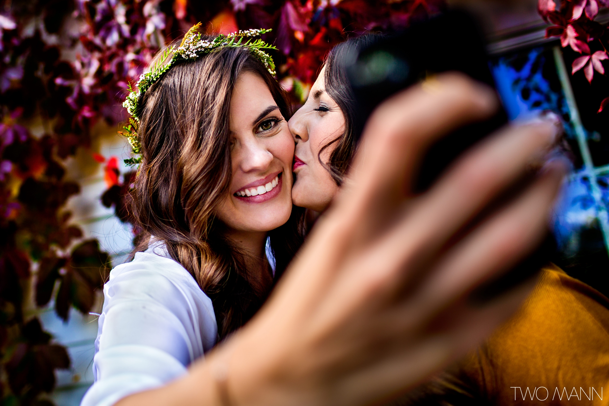 bride taking a picture of a friend and herself hugging together with her phone