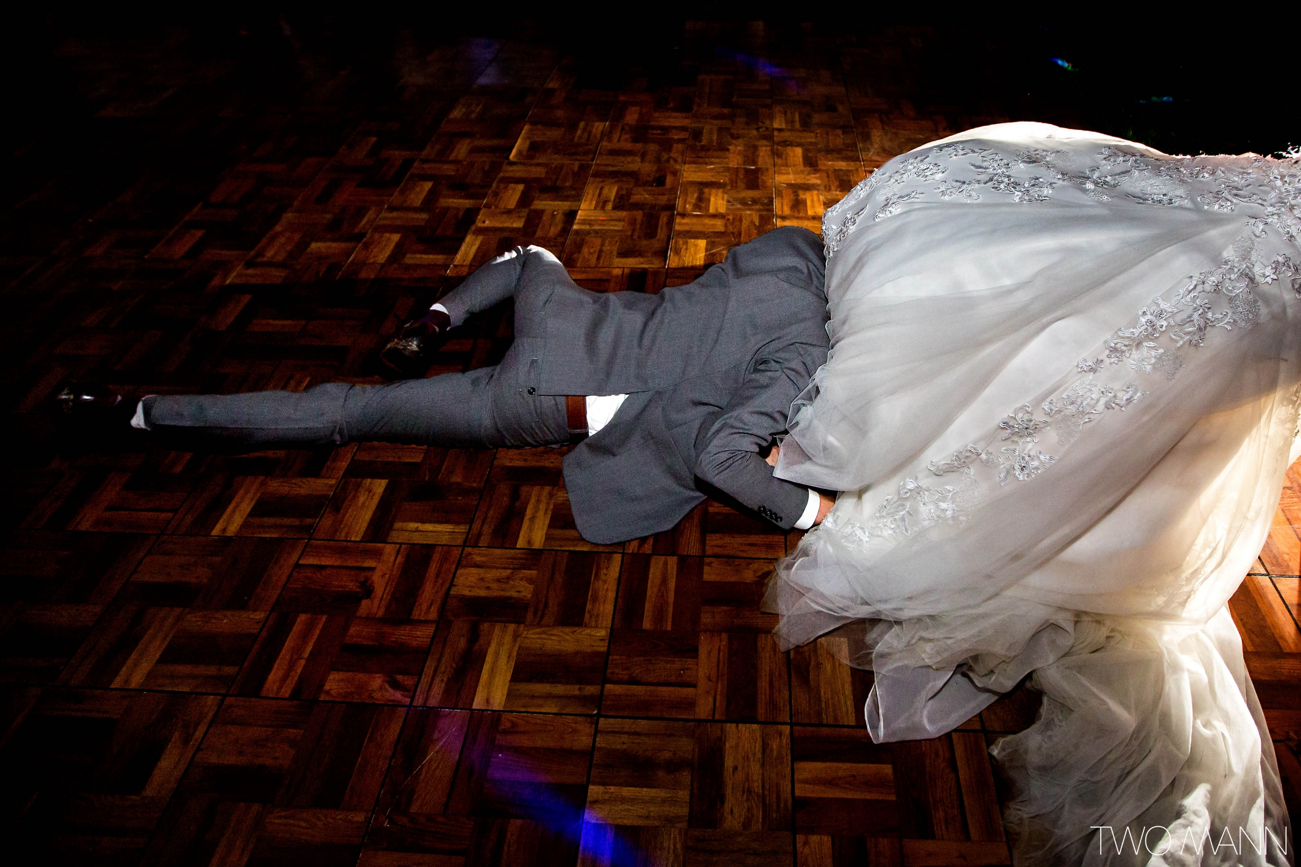 a groom lying on the dance floor with face hiding under bride's dress trains