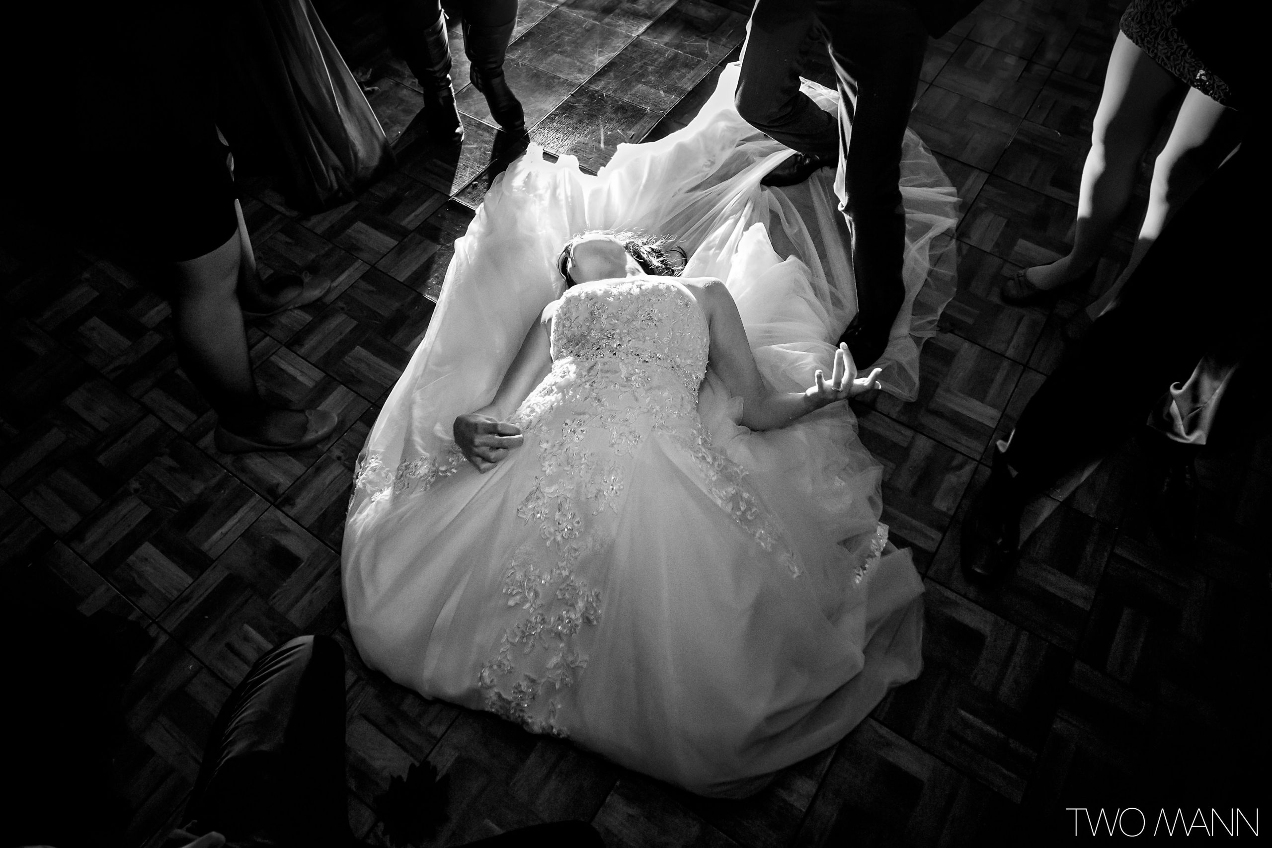 a bride lying on her dress train during a dance