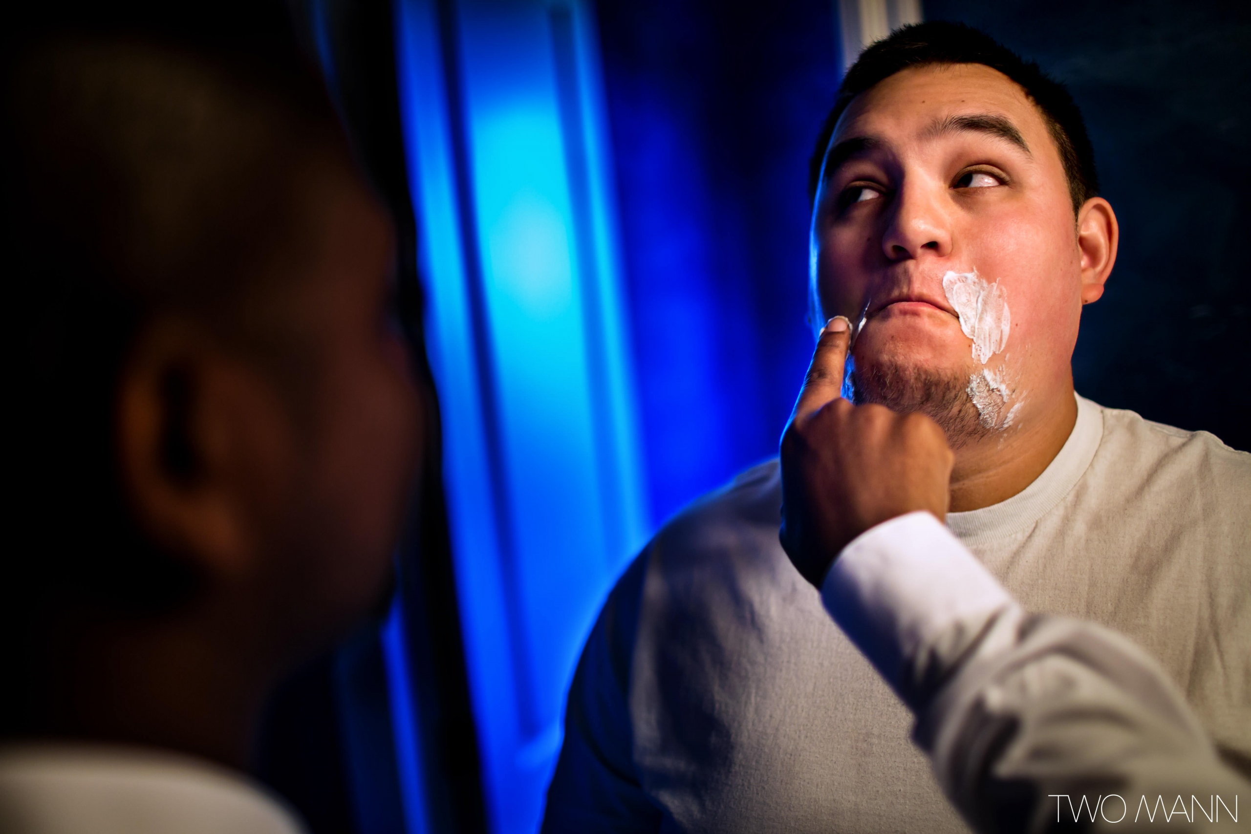 a friend helping a groom apply shaving cream