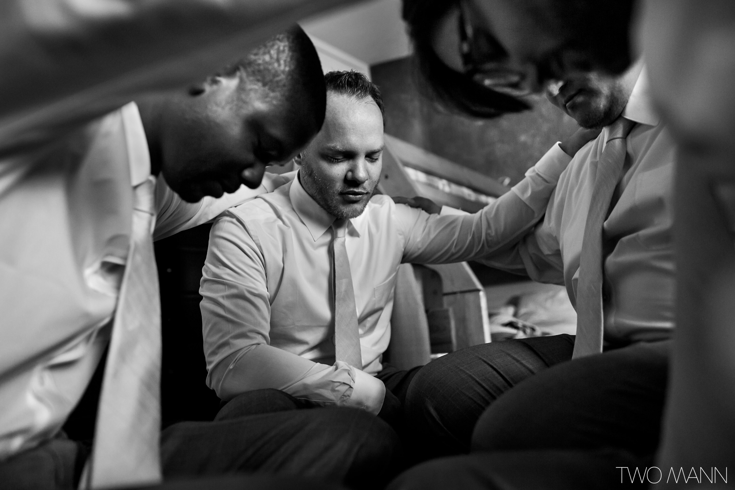 groom and groomsmen pray together