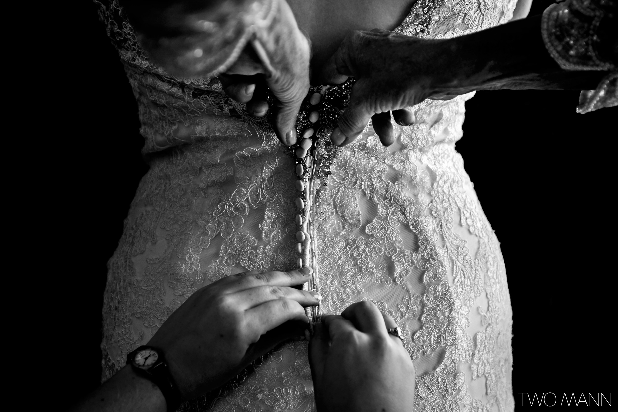 helping the bride zip up the wedding dress with back zipper