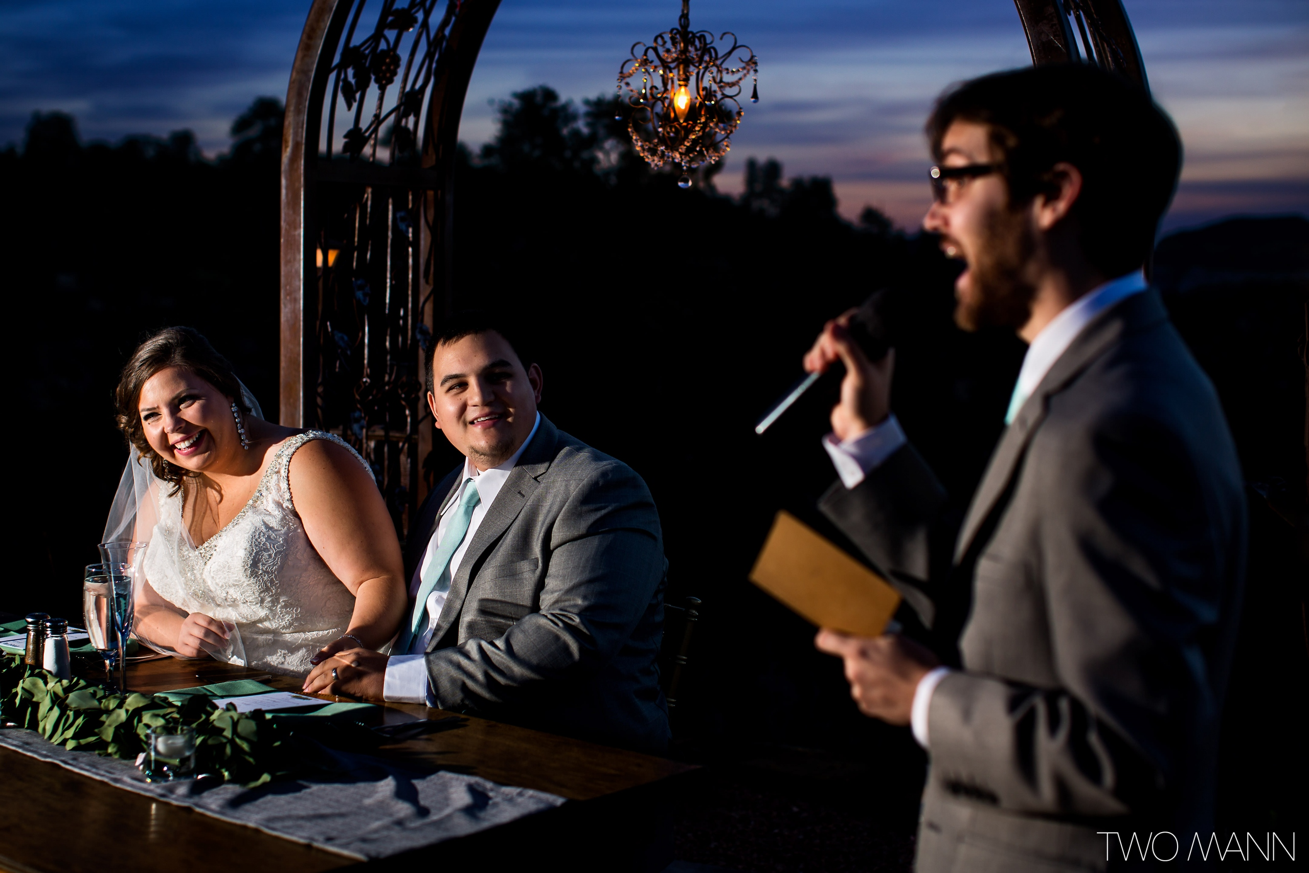 newlyweds enjoying speech of a wedding guest