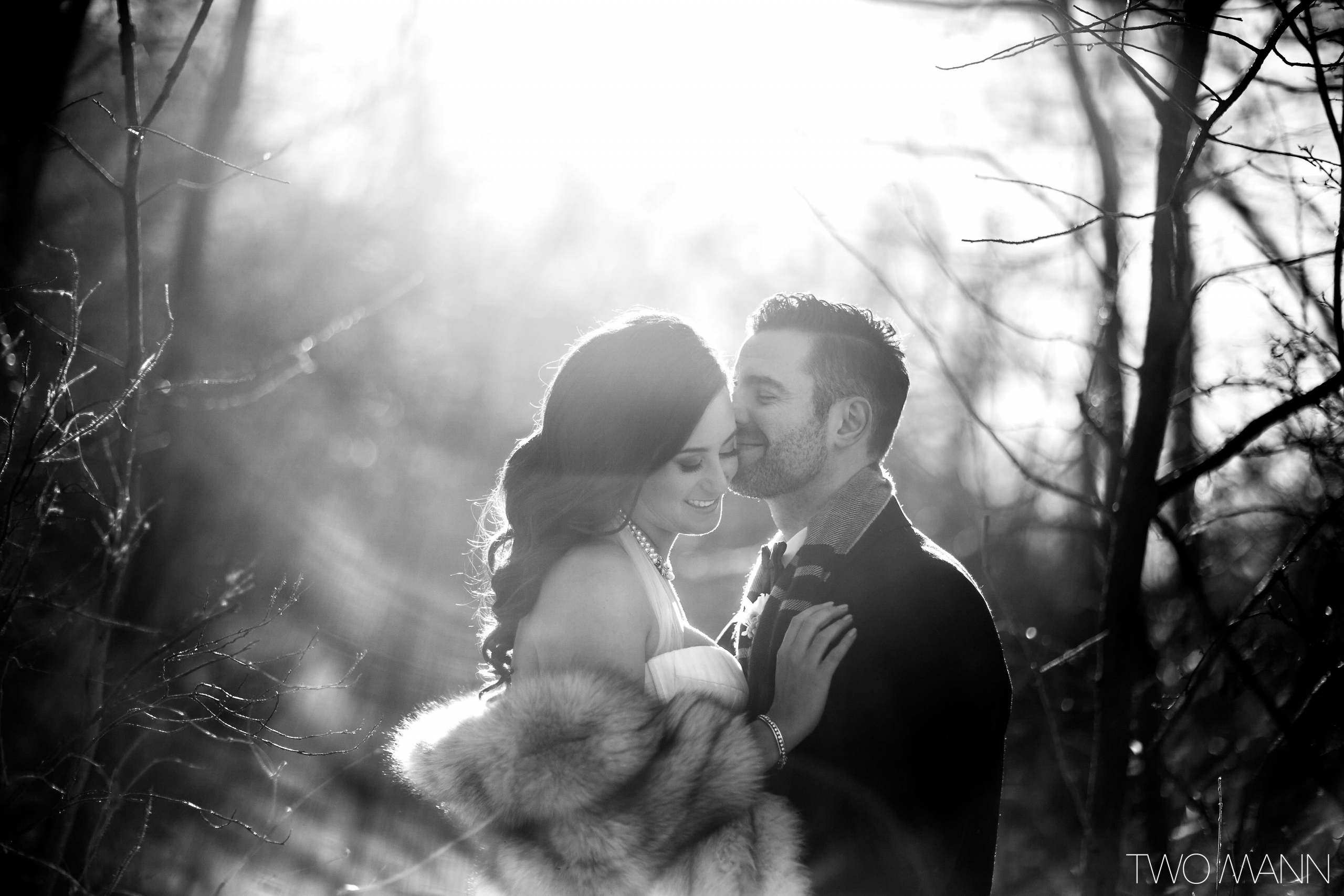 a groom kissing his bride on the cheek in the winter forest