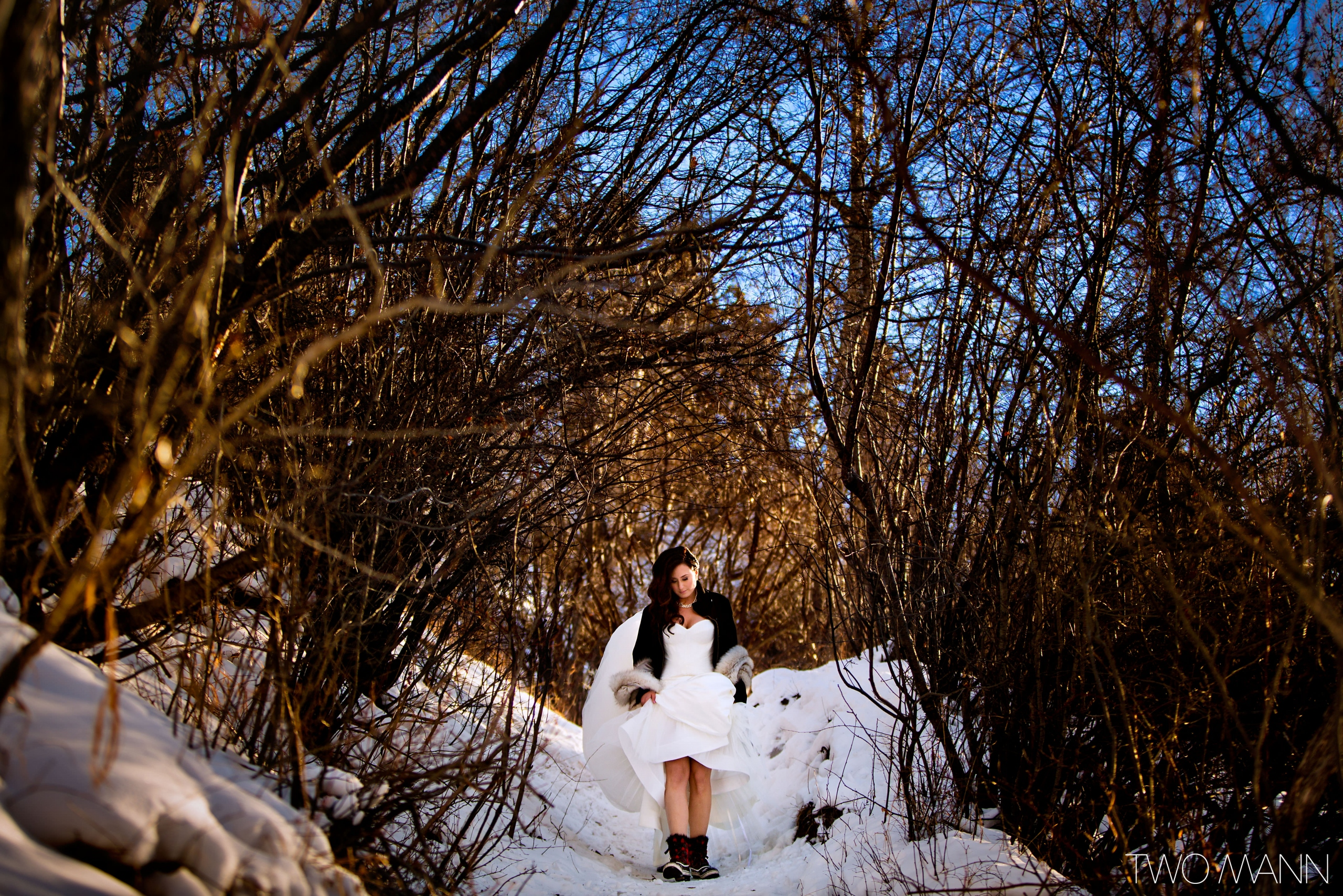 a bride with boots walking in snow-covered forest