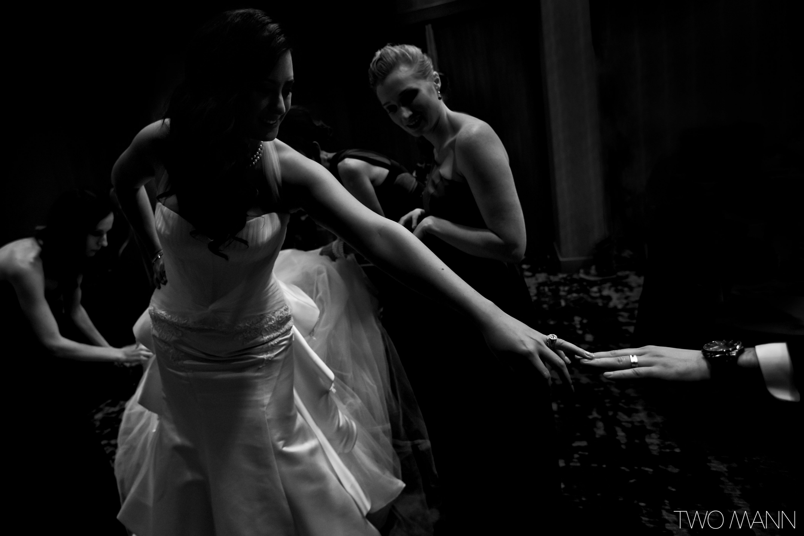 bride greeting with a guest while others arranging her dress train