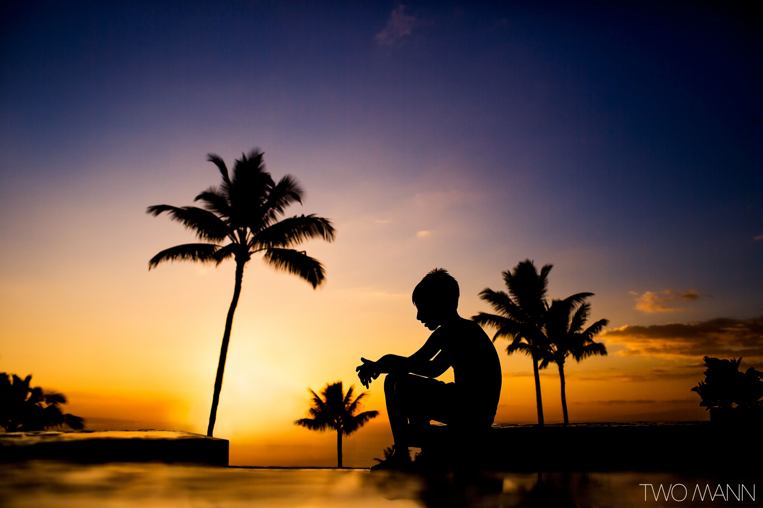 boy sitting at tropical beach at sunset in Maui