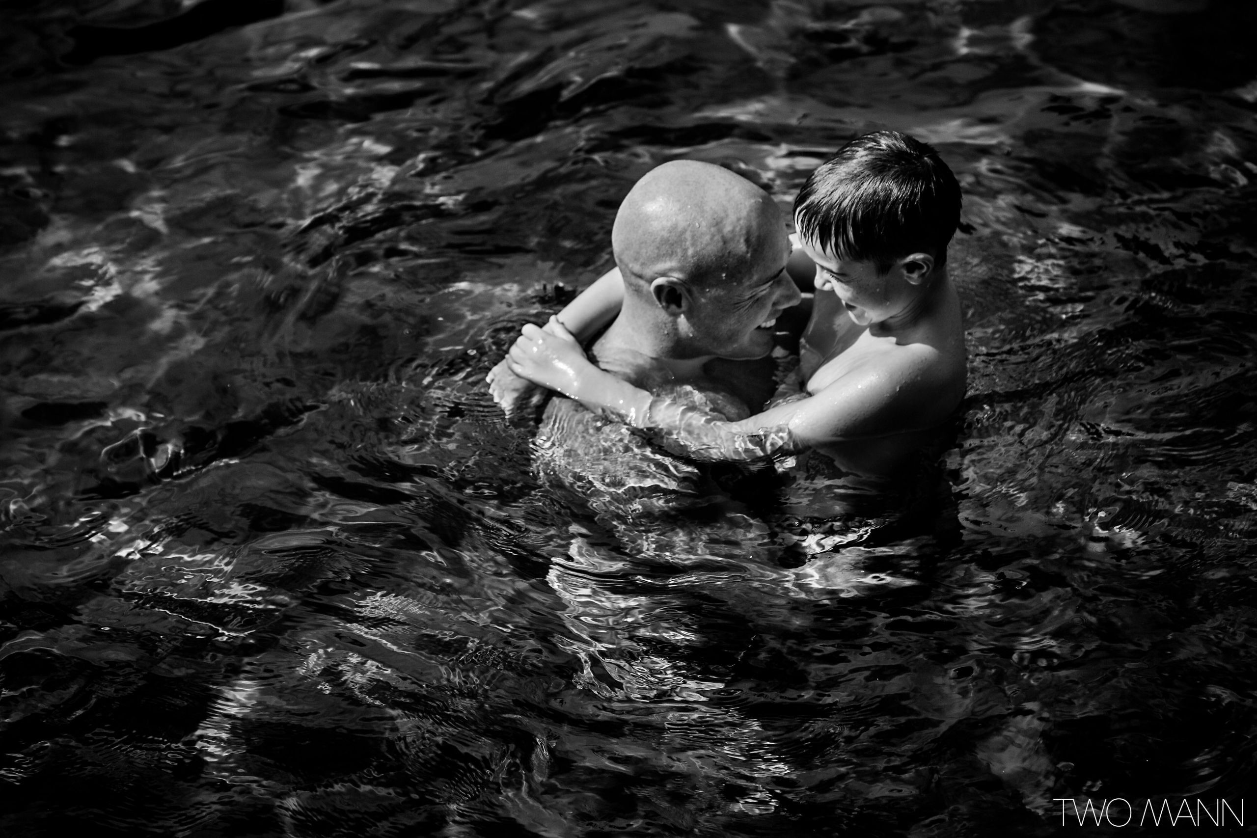 a groom and his son hugging in a pool in Maui