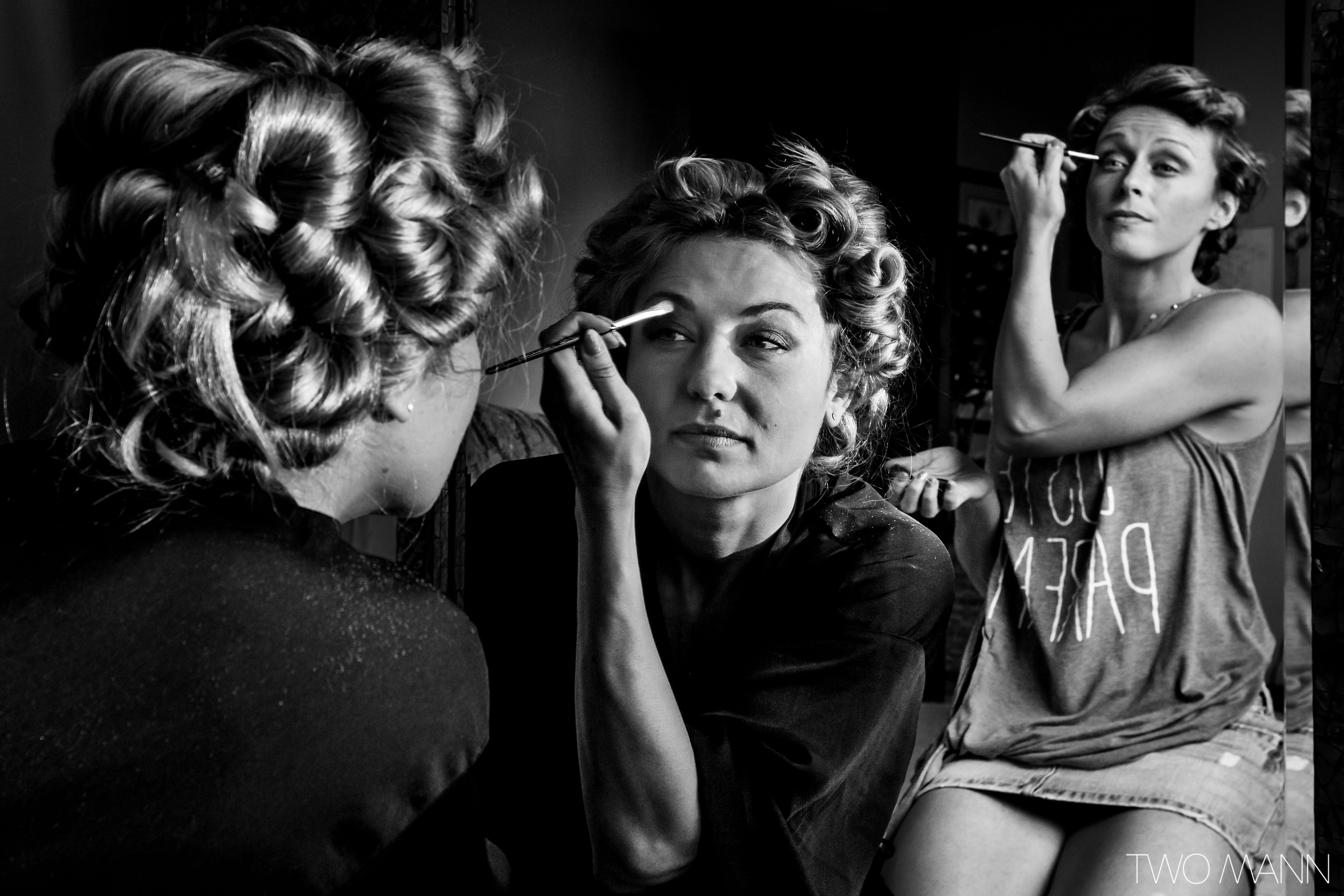 bride and bridesmaid doing their makeups in front of a mirror