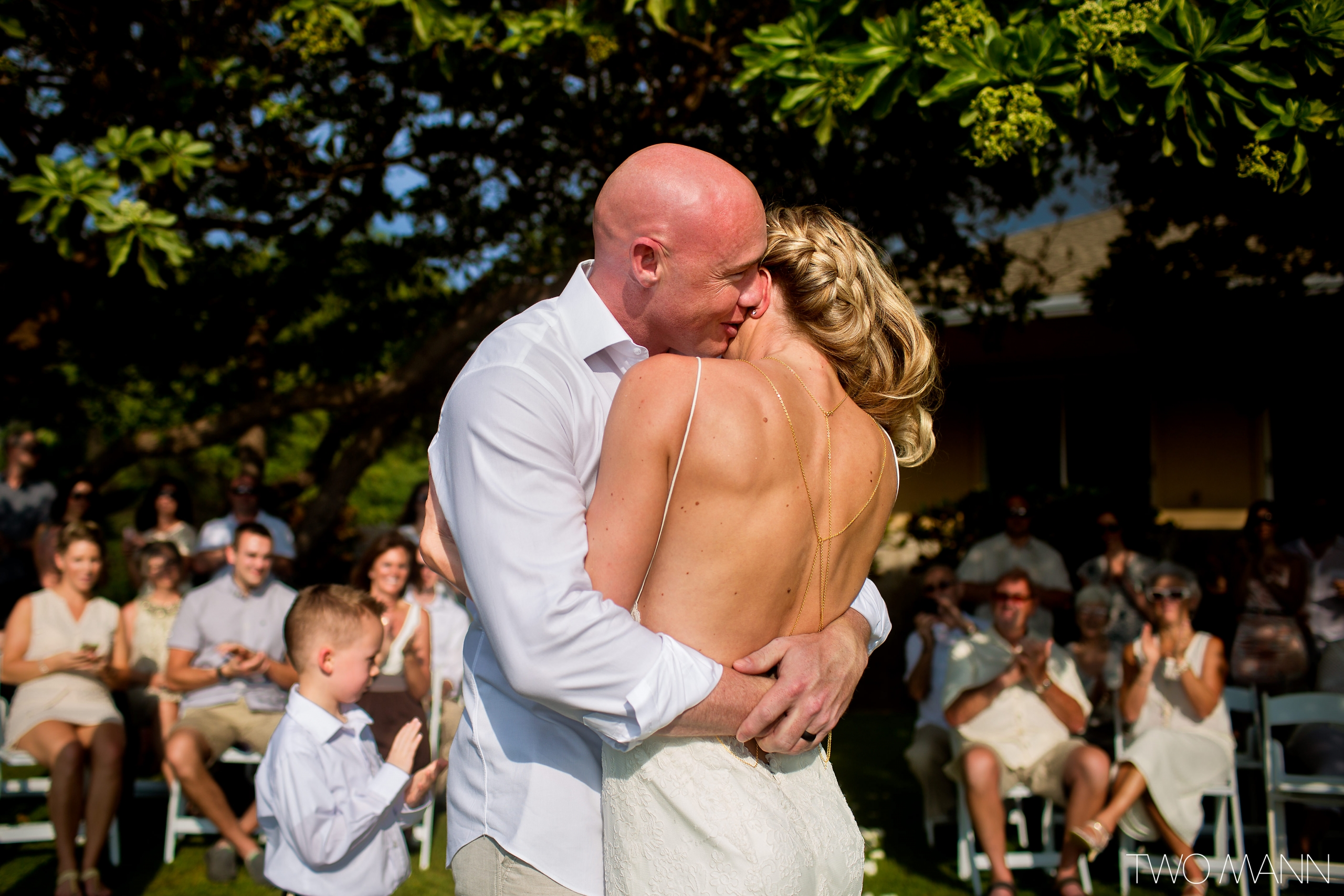 a groom embracing his-bride at a wedding ceremony in Maui