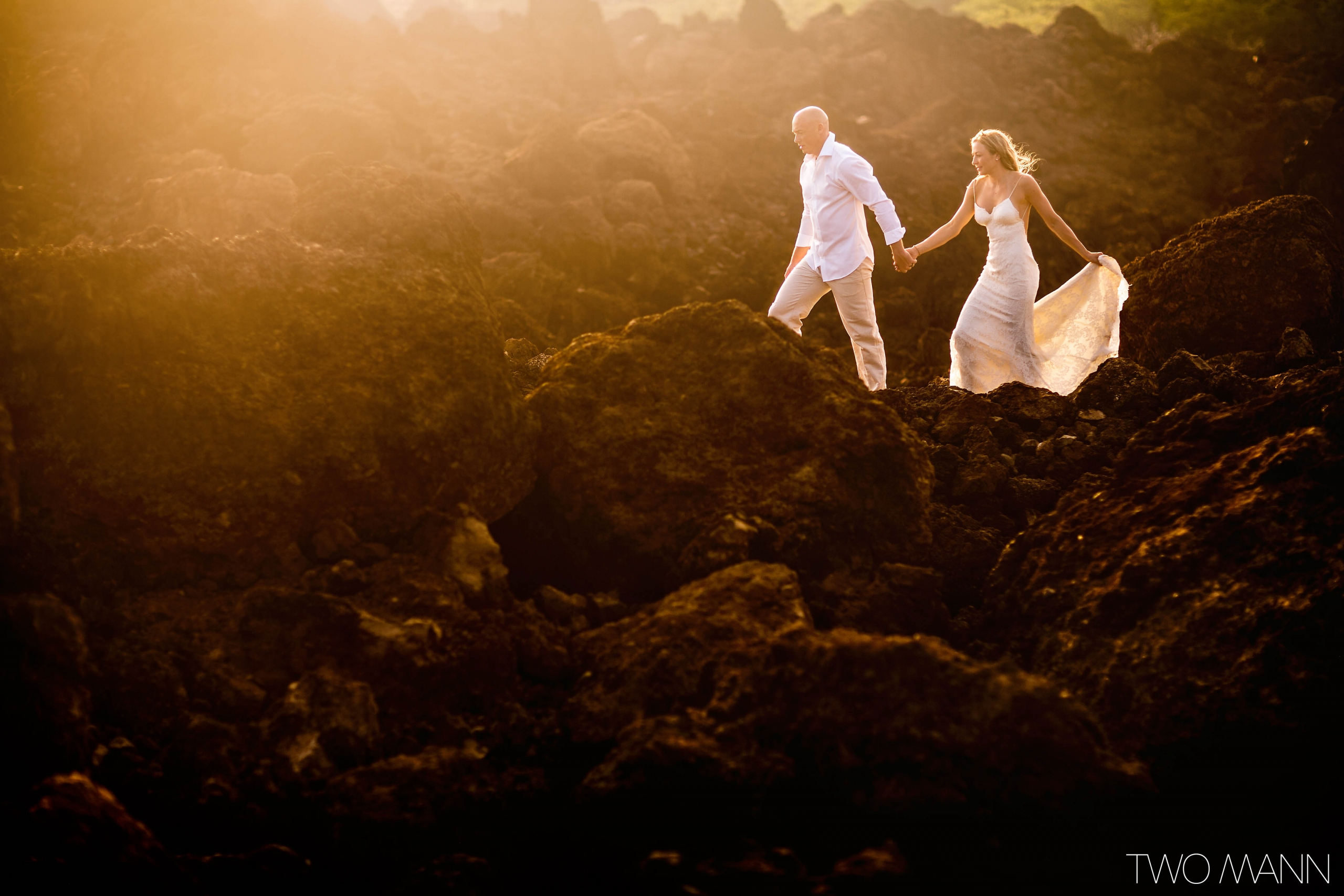 groom holding bride's hand walking on lava rocks in Maui