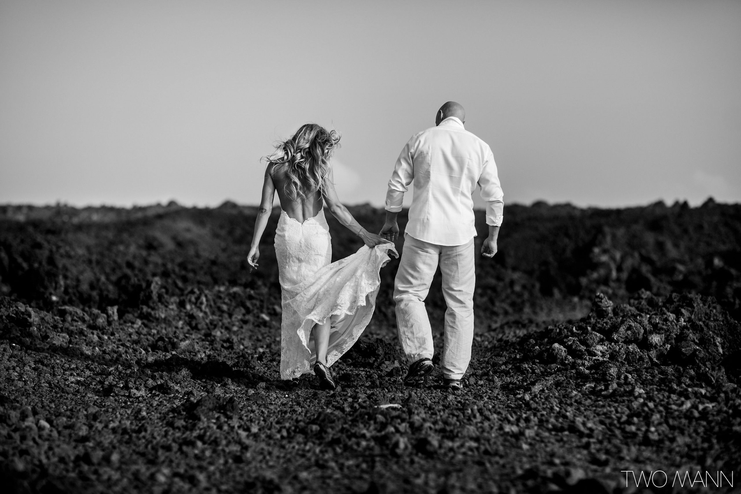 back view of bride and groom walking on lava stones in Maui
