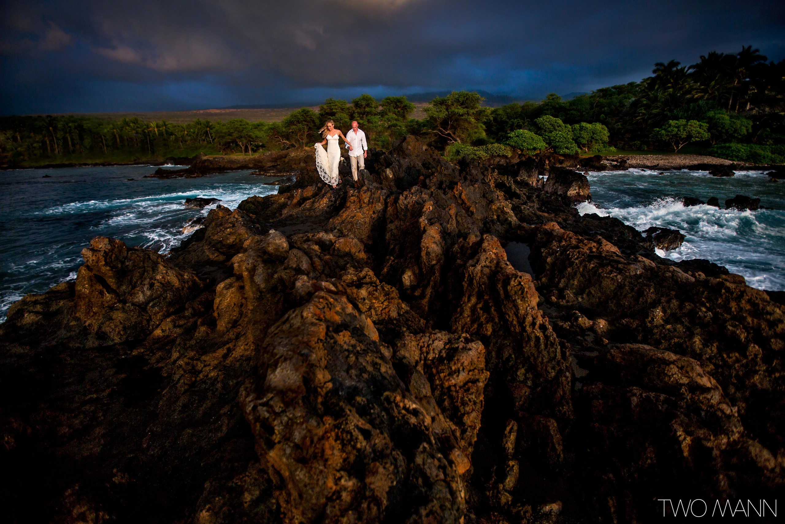 bride and groom walking on lava rocks by ocean-side at sunset in Maui