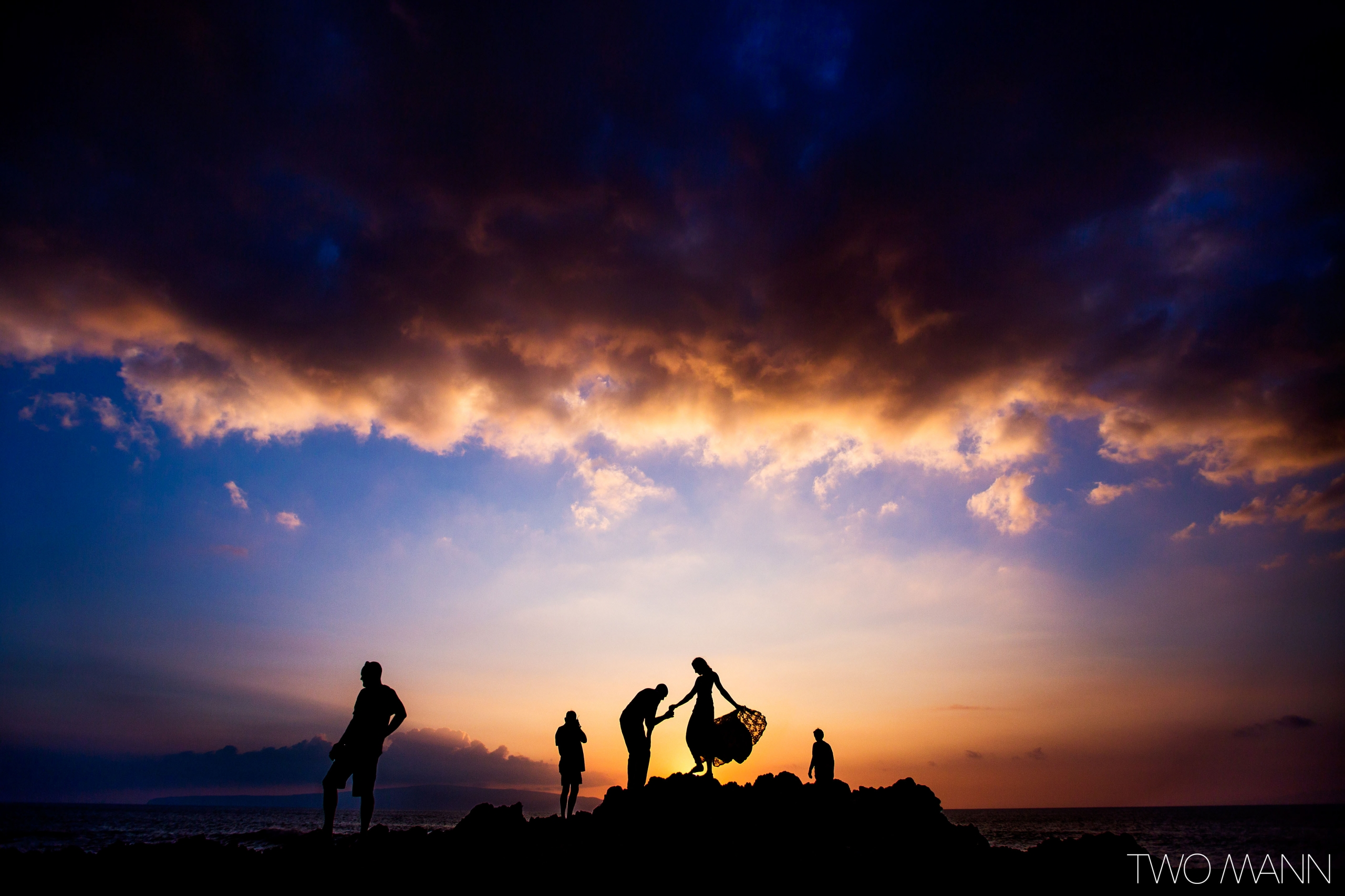 newlyweds and friends on lava rocks by ocean-side at sunset in Maui