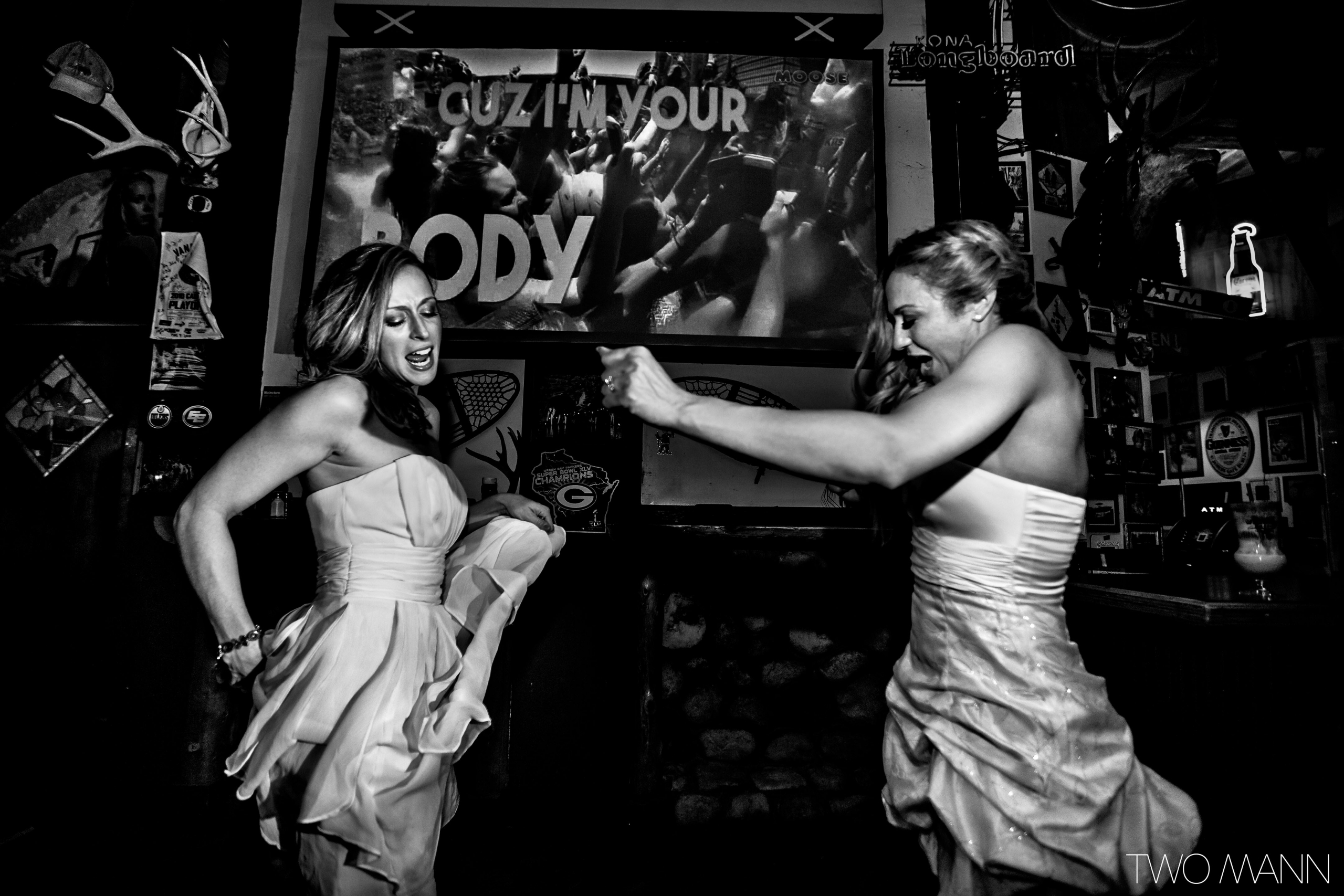 a bride and friend dancing at reception