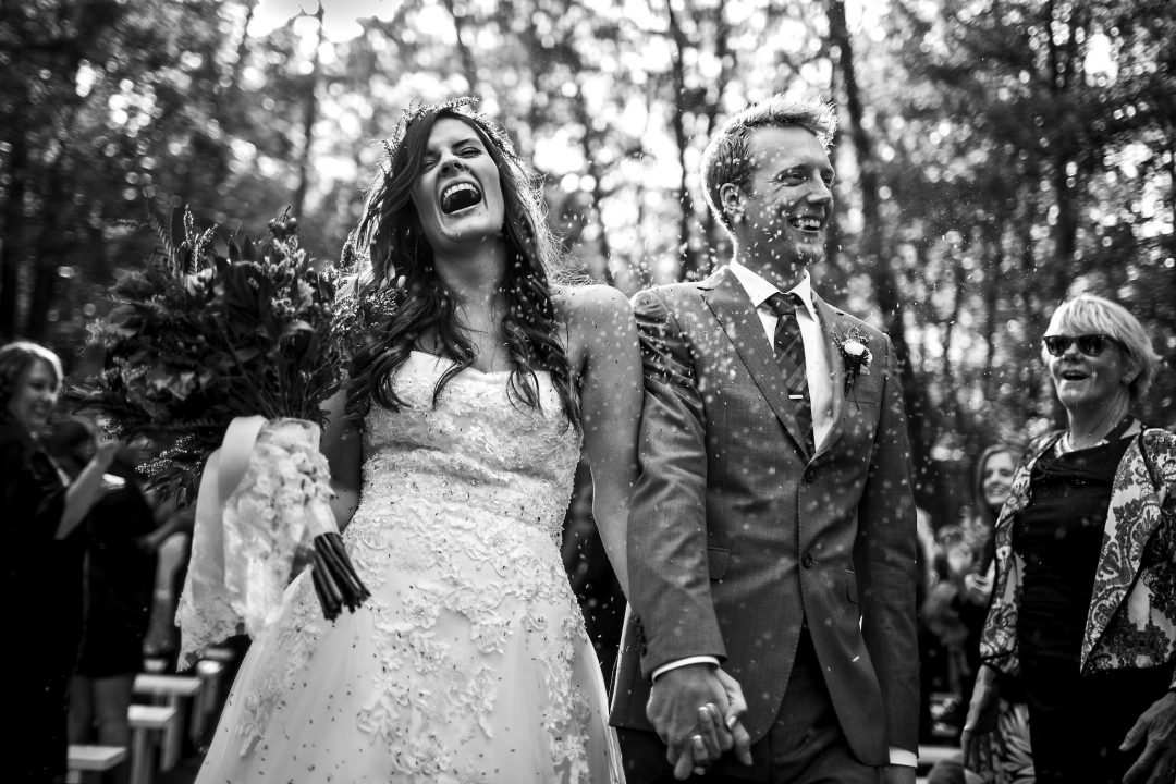 Bride and groom walking down the aisle filled with laughter