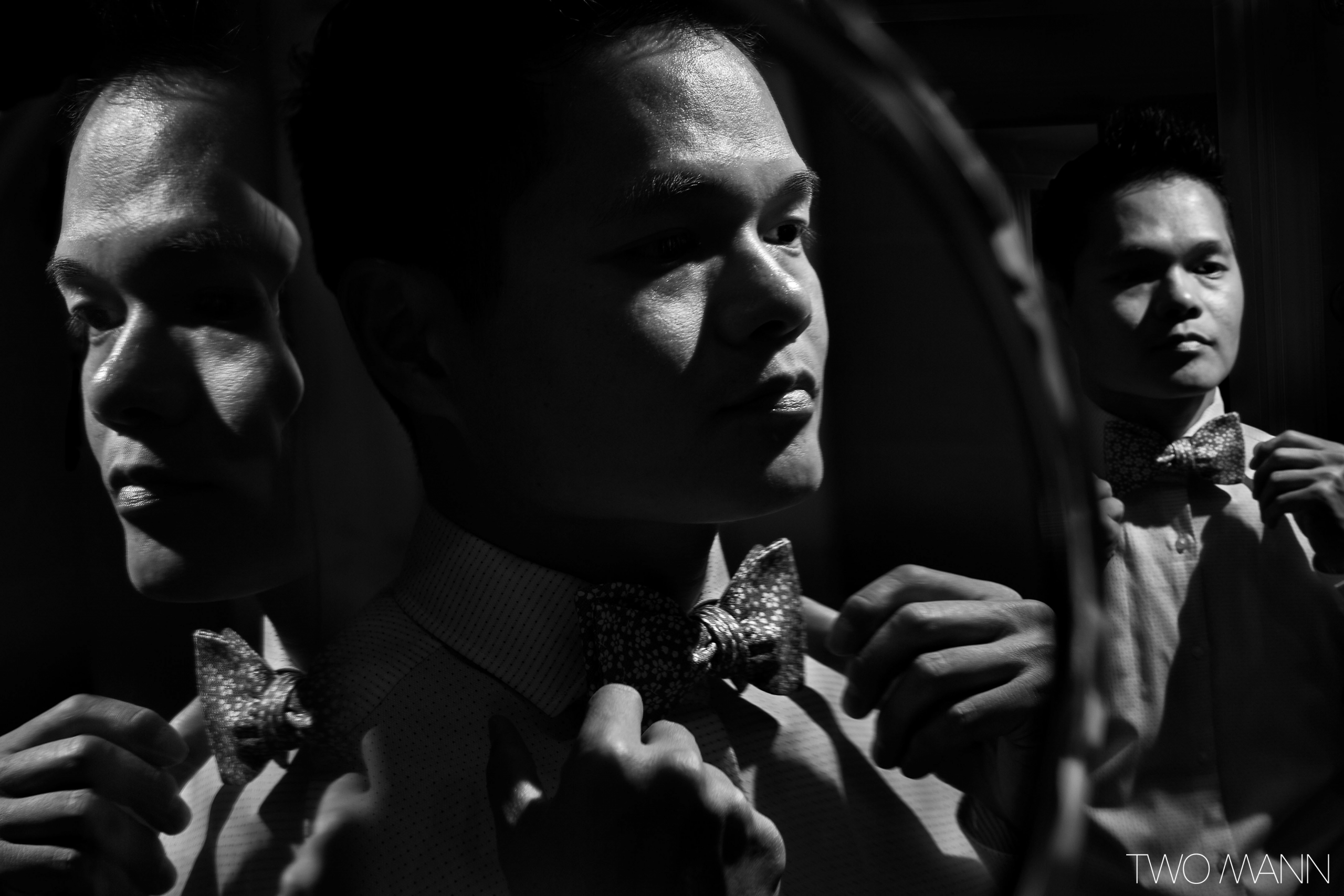 a groom tying a bow tie in front of a mirror