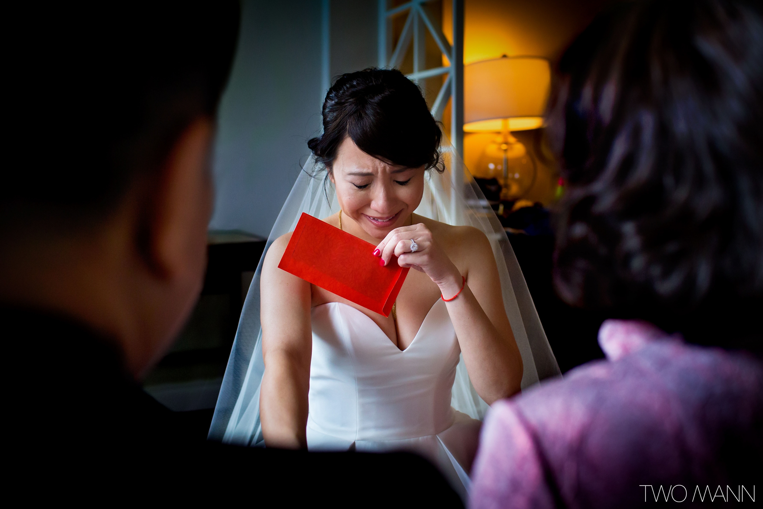 tearful bride with red packet in hand at tea ceremony