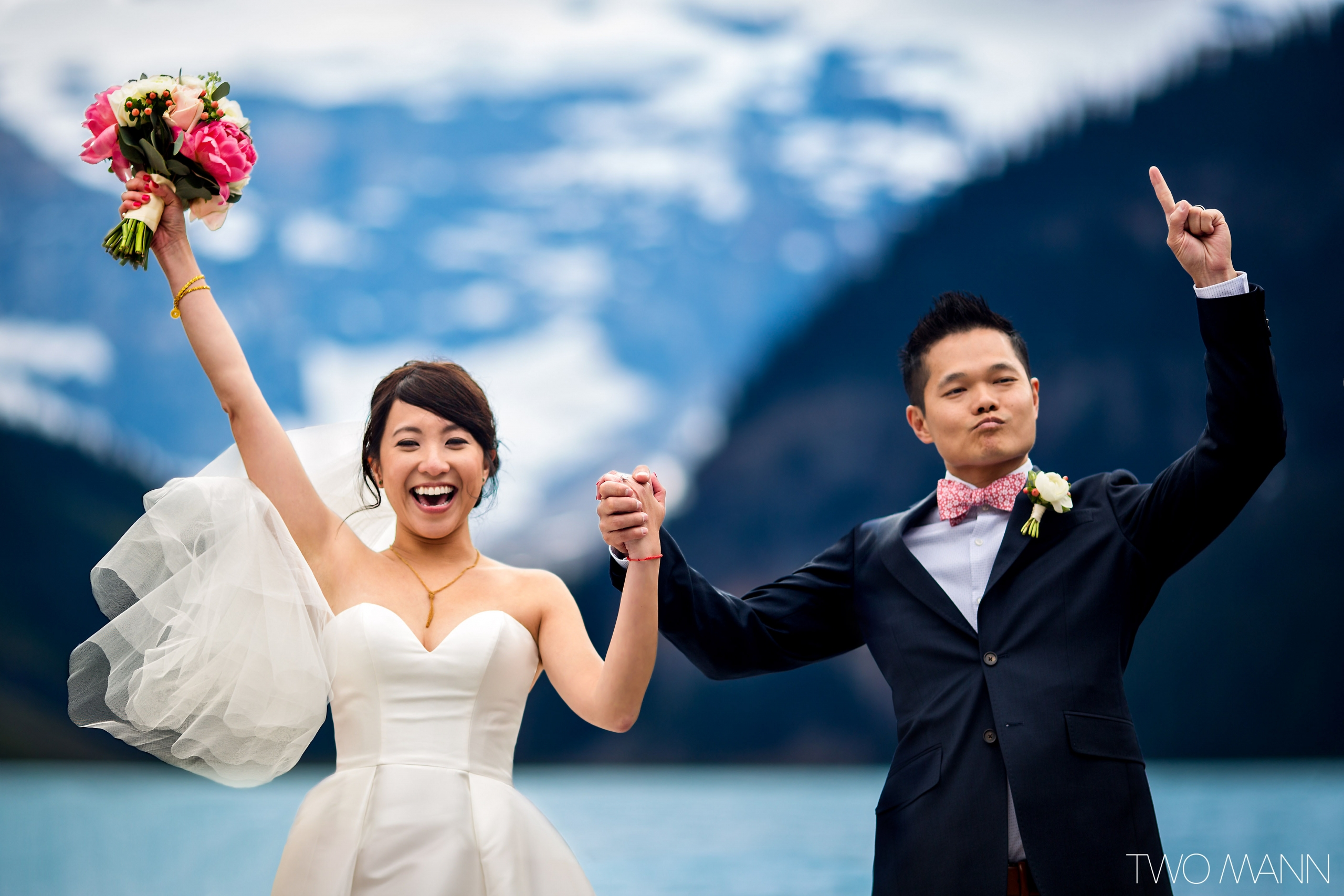 bride and groom cheering at getting married by the shores of Lake Louise