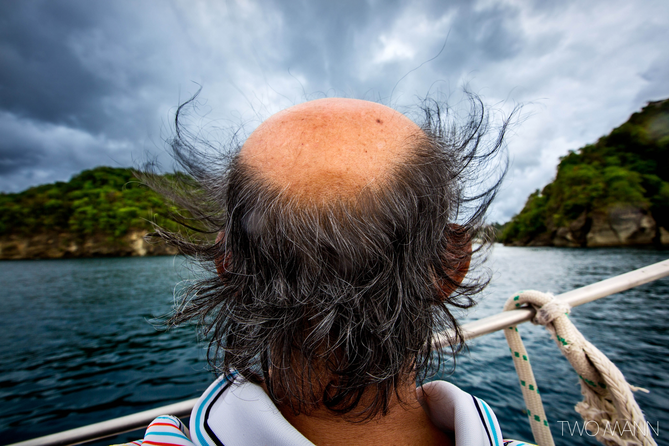 a balding-on-top-of-head man looking at the sea