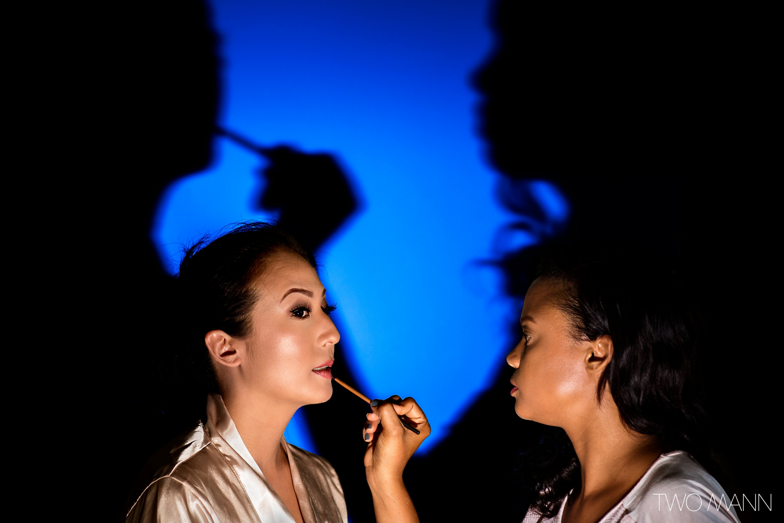 a makeup artist applying lipstick for the bride