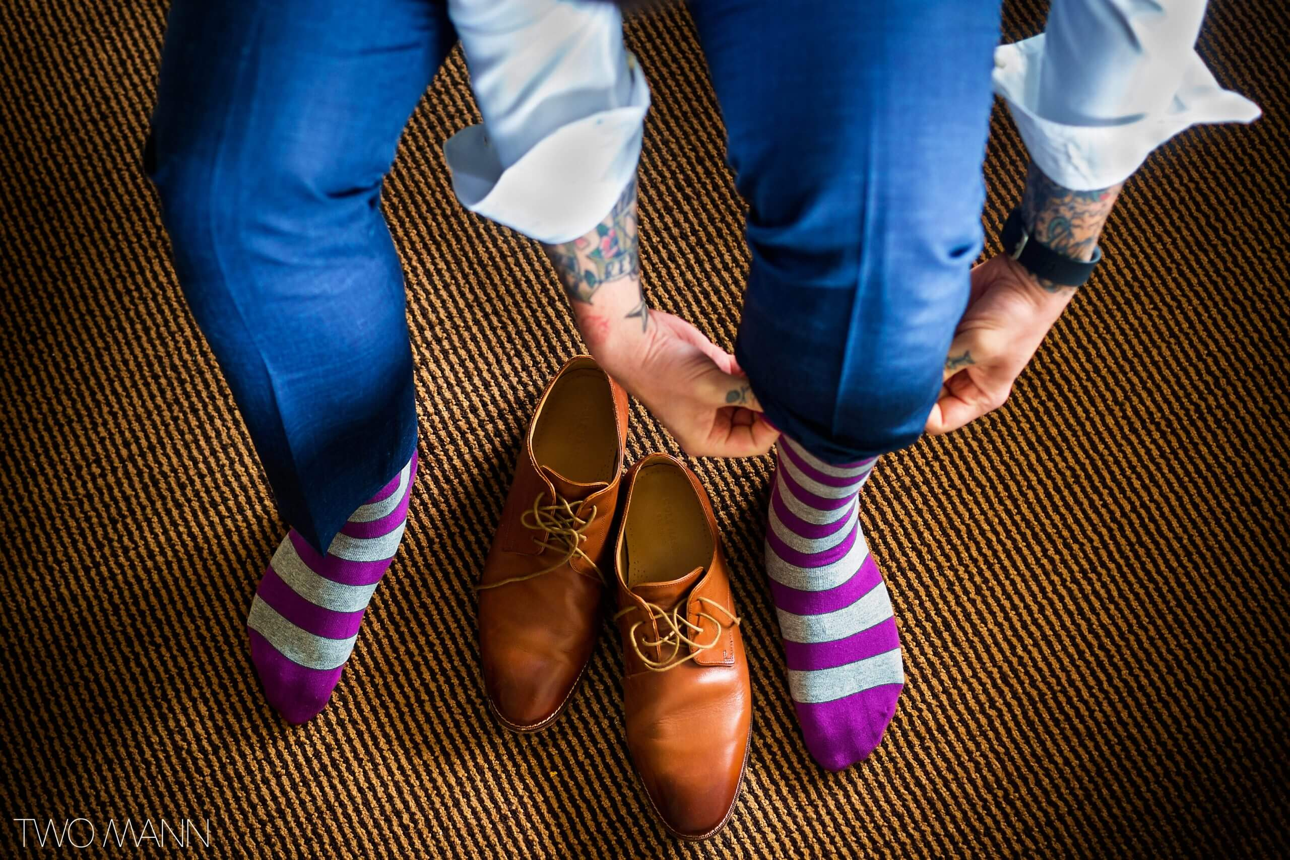 newlywed husband putting on socks before wedding ceremony