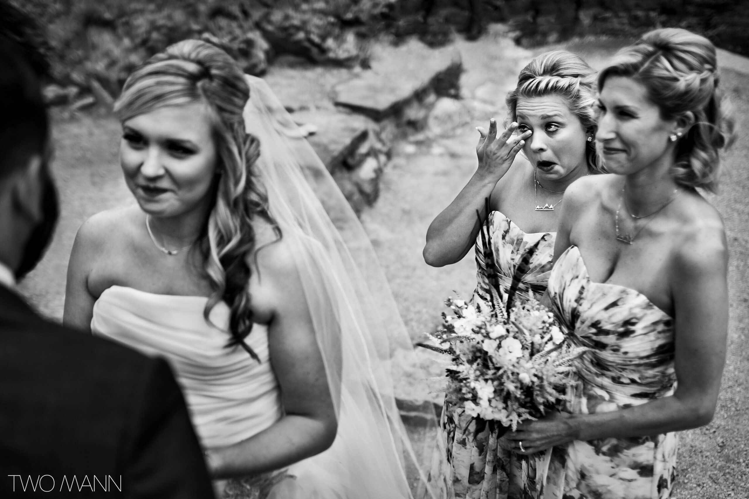 bridesmaid smiling and shedding tears at wedding ceremony
